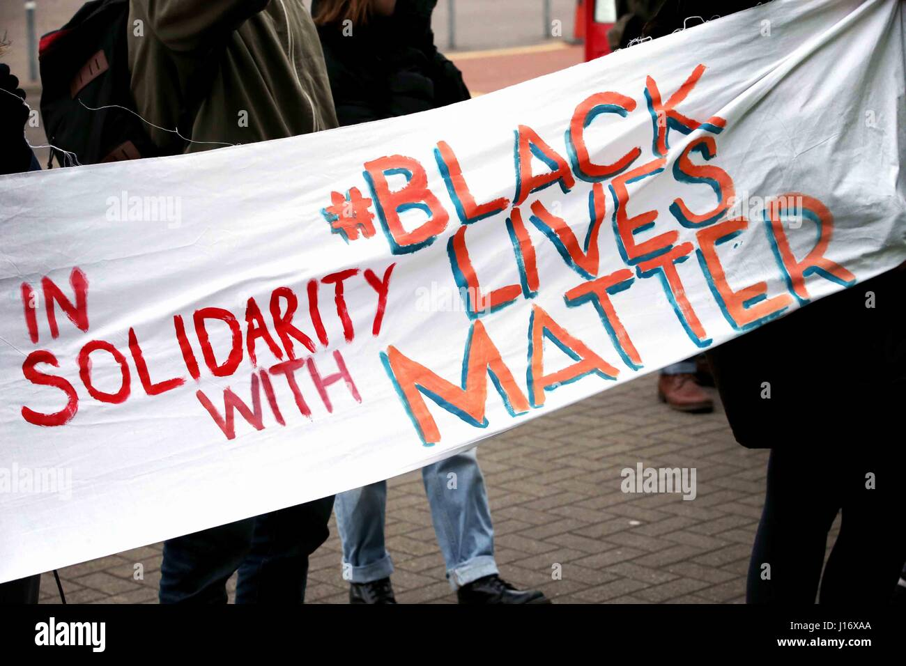People hold up a sign reading 'In solidarity with Black Lives Matter'. - Stock Image
