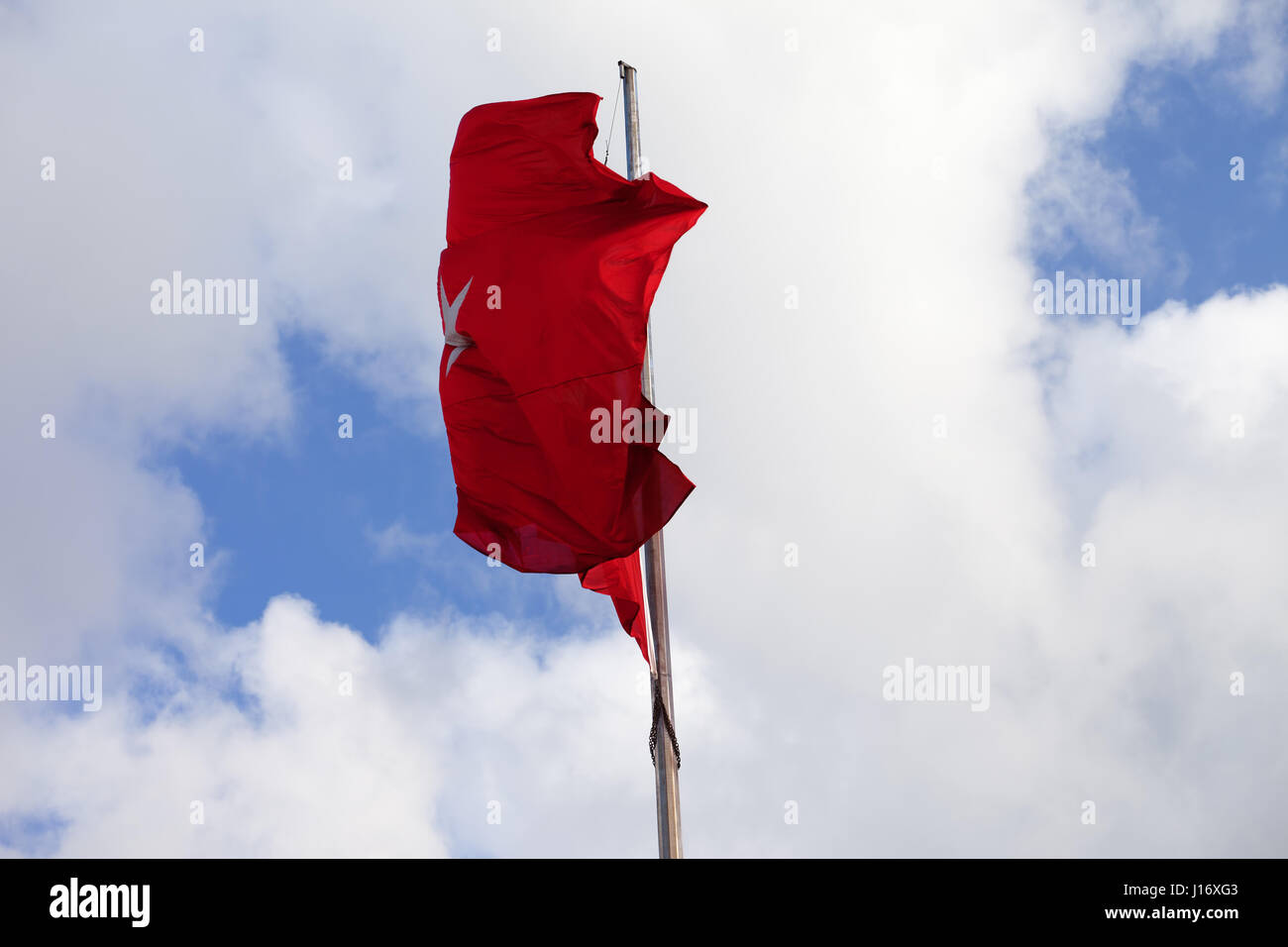 Turkish flag on flagpole waving in wind at sky with clouds - Stock Image