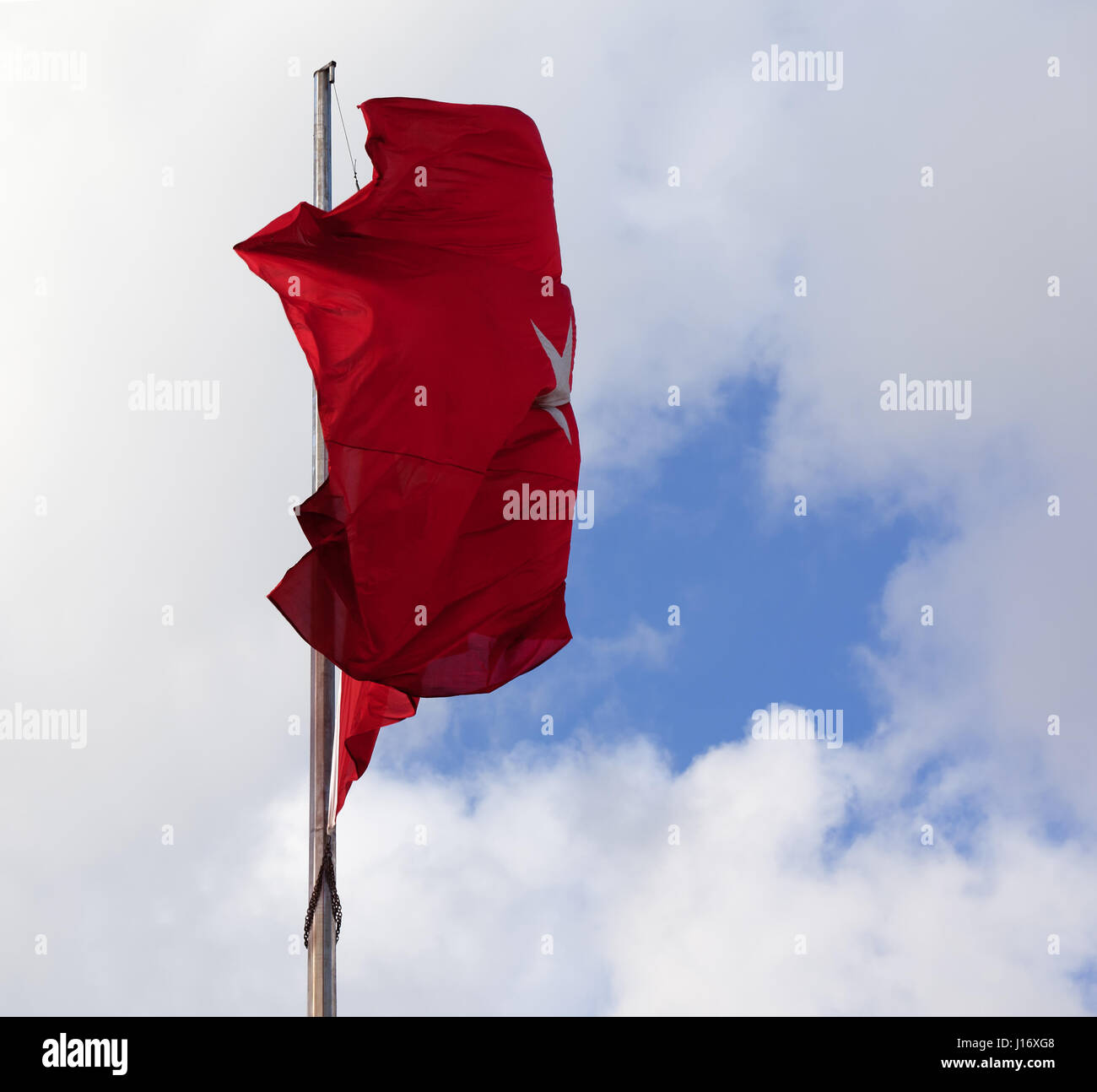 Turkish flag on flagpole waving in wind at sky with sunlight clouds - Stock Image