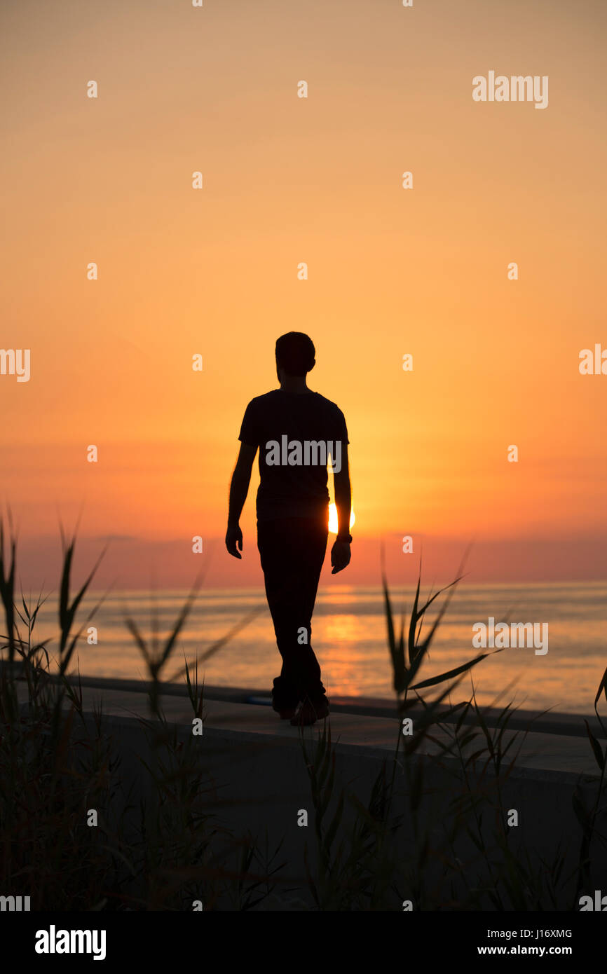 Full length silhouette of a male figure walking on the beach at sunset - Stock Image