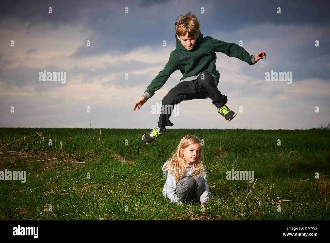 Brother Jumping Over Sister In Meadow Cloudy Sky Background Children Summer Outdoor Activities Jumping High And Far