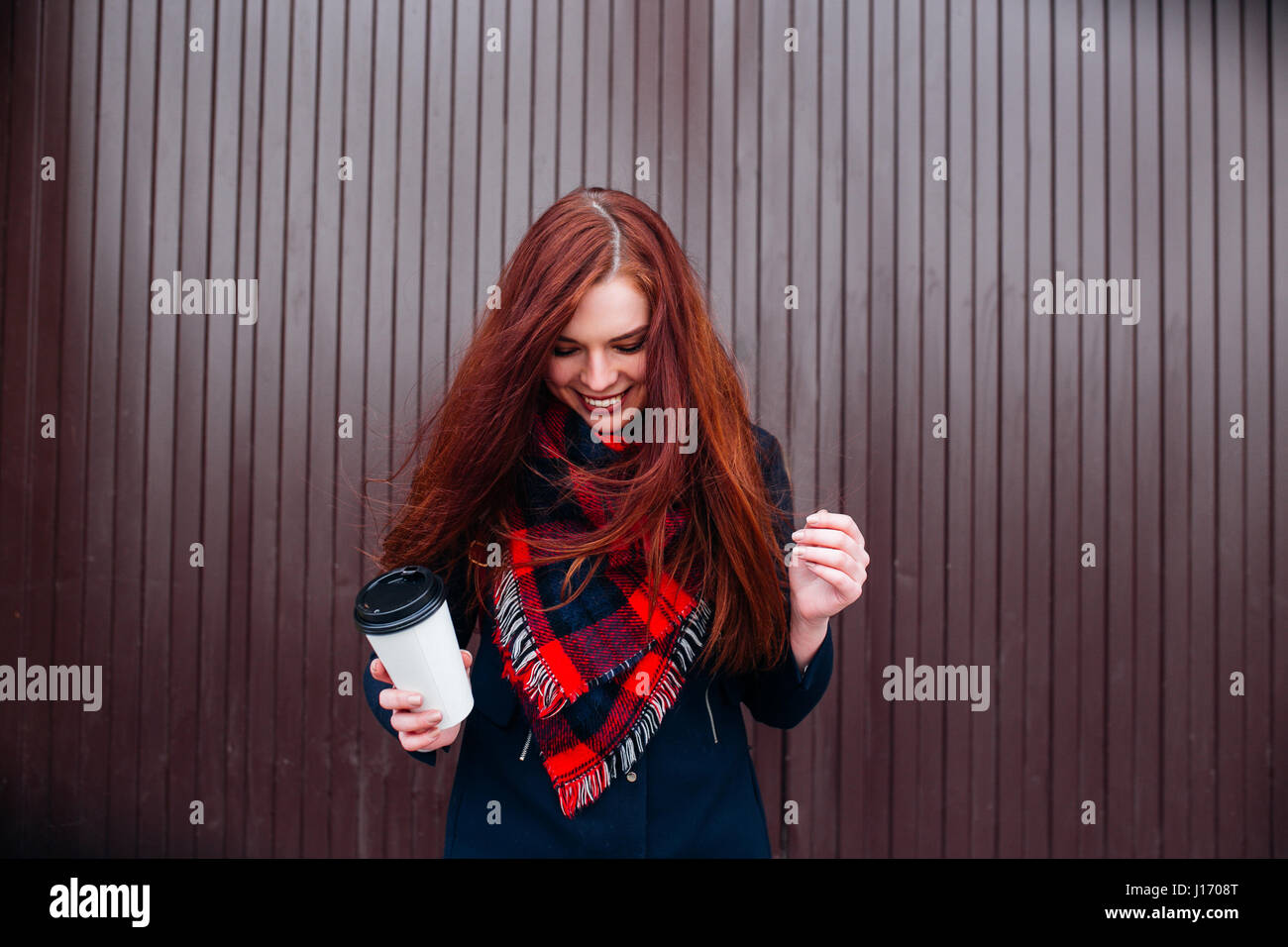 Beautiful happy young woman holding a paper cup and drinking coffee. Cheerful woman with red long hair in the street - Stock Image