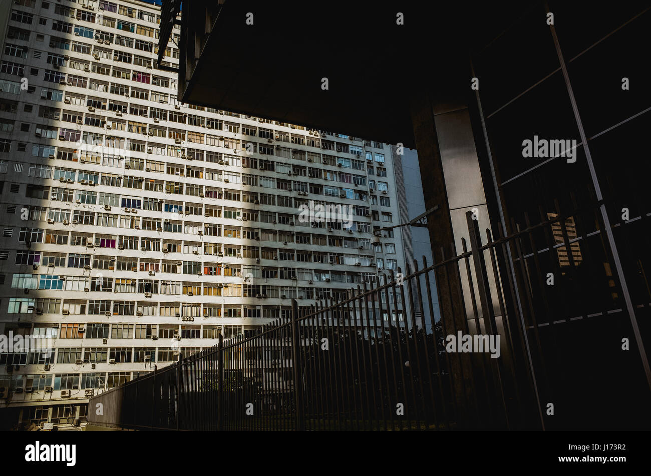 Overpopulated high rise building next to building with high security measures in Downtown Rio de Janeiro, Brazil - Stock Image