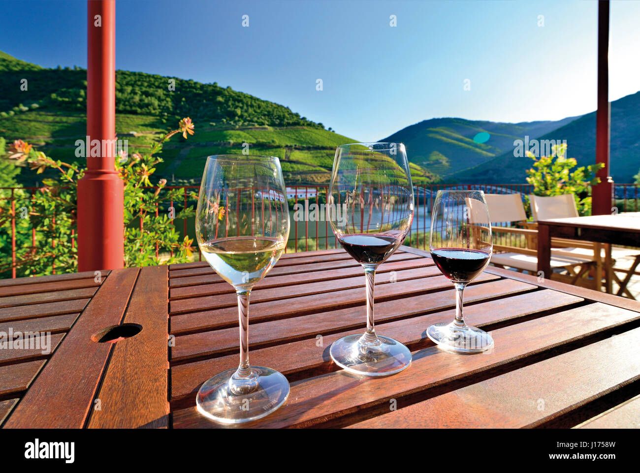Portugal: Three wine glasses on a table with great view of river Douro - Stock Image
