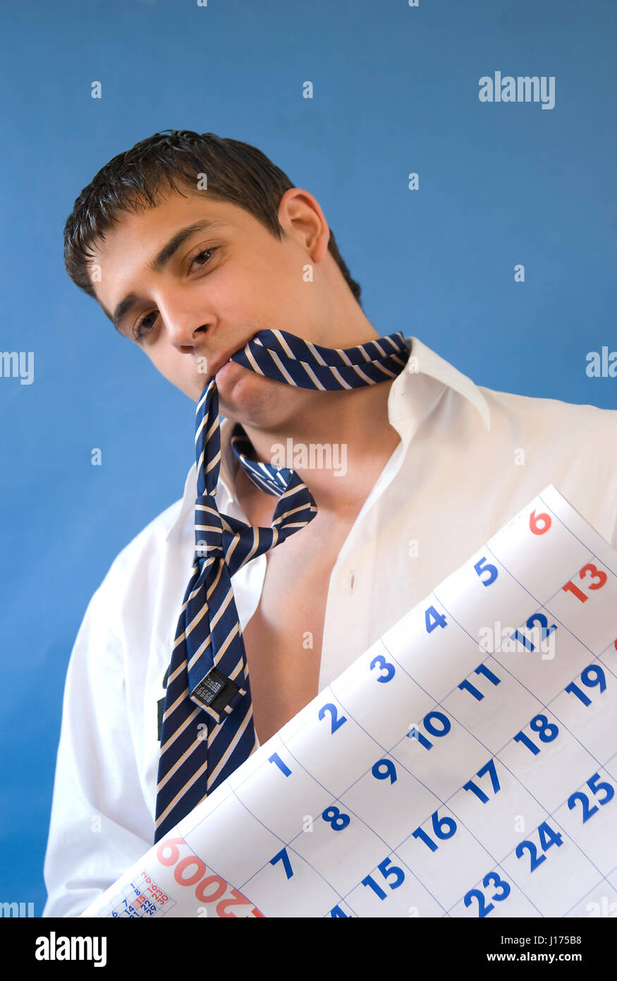 Stressed man biting his tie, holding a calendar. - Stock Image