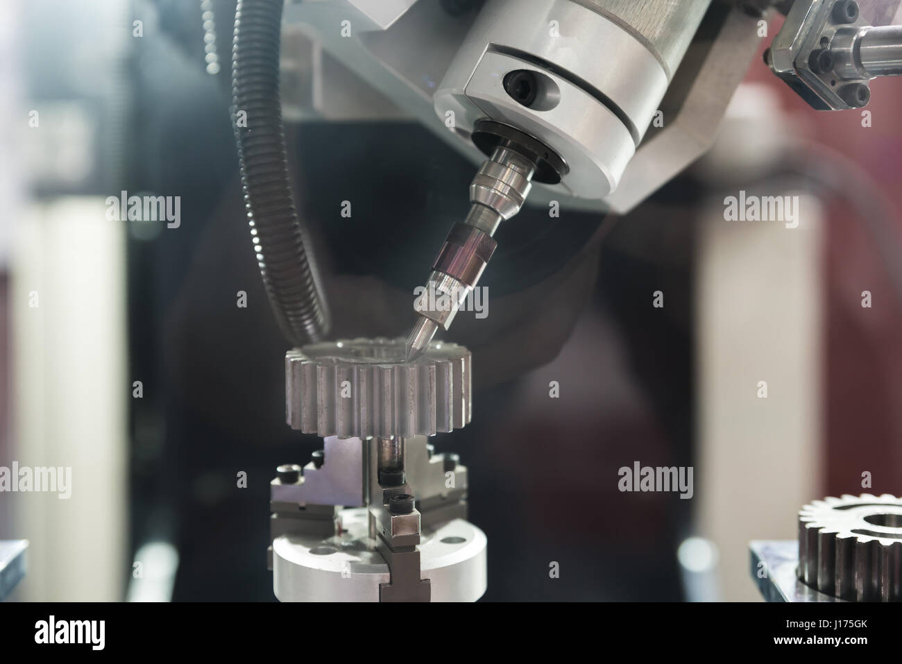 The five-axis Computer Numerical Control (CNC) machine while cutting sample gear part. Indutrial machine. - Stock Image