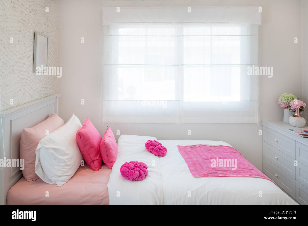 Interior of White bedroom with double bed and pink pillows and bookshelf at home. Stock Photo