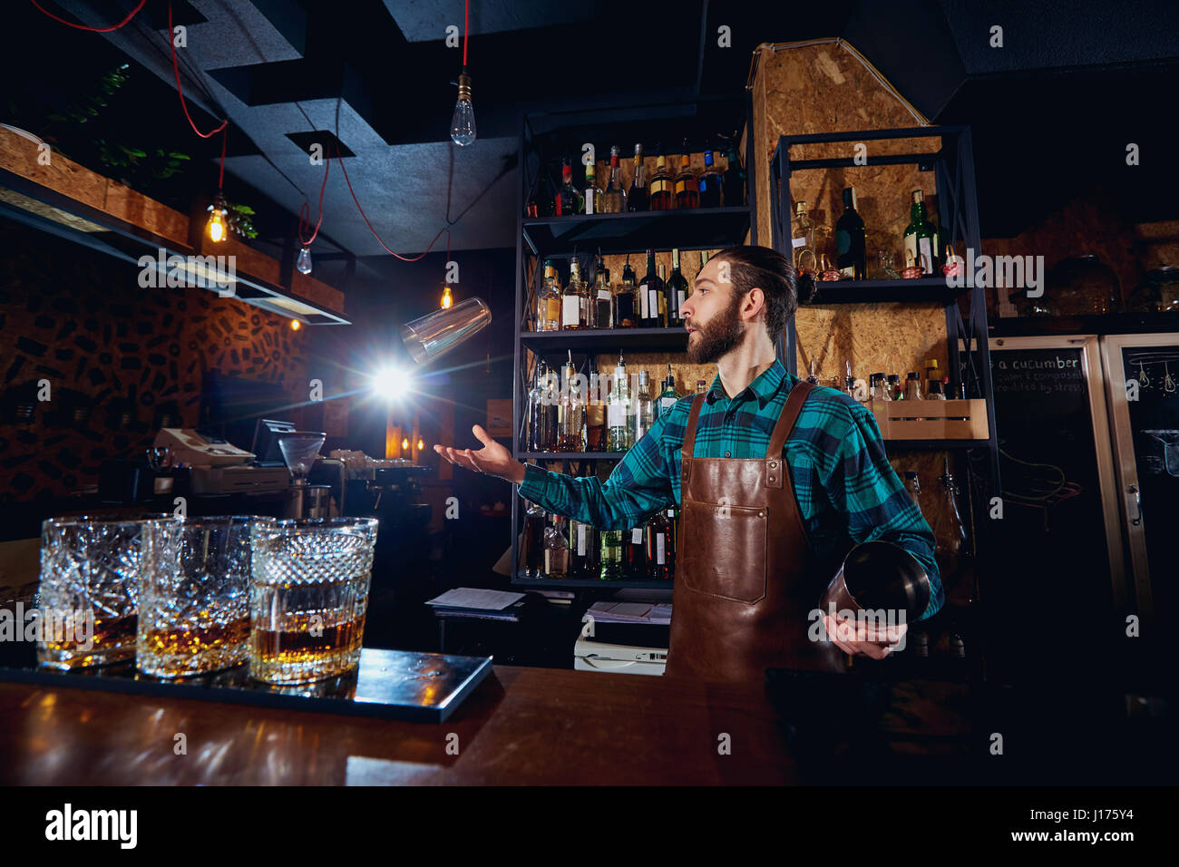 The barman juggler throws up a glass for  cocktail at bar - Stock Image