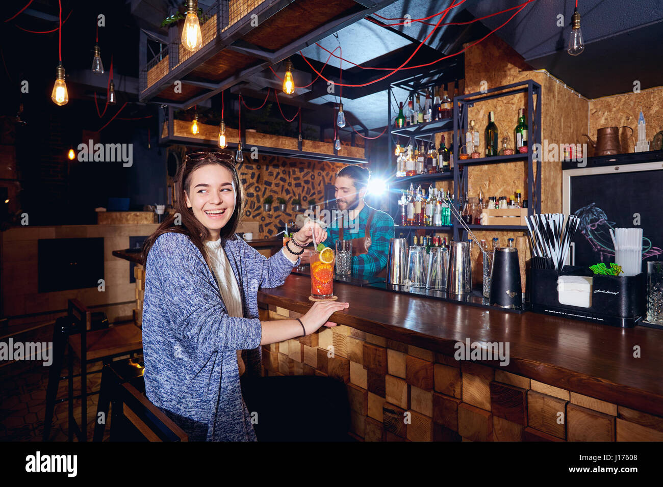A visitor girl smiles in  bar with  cocktail - Stock Image
