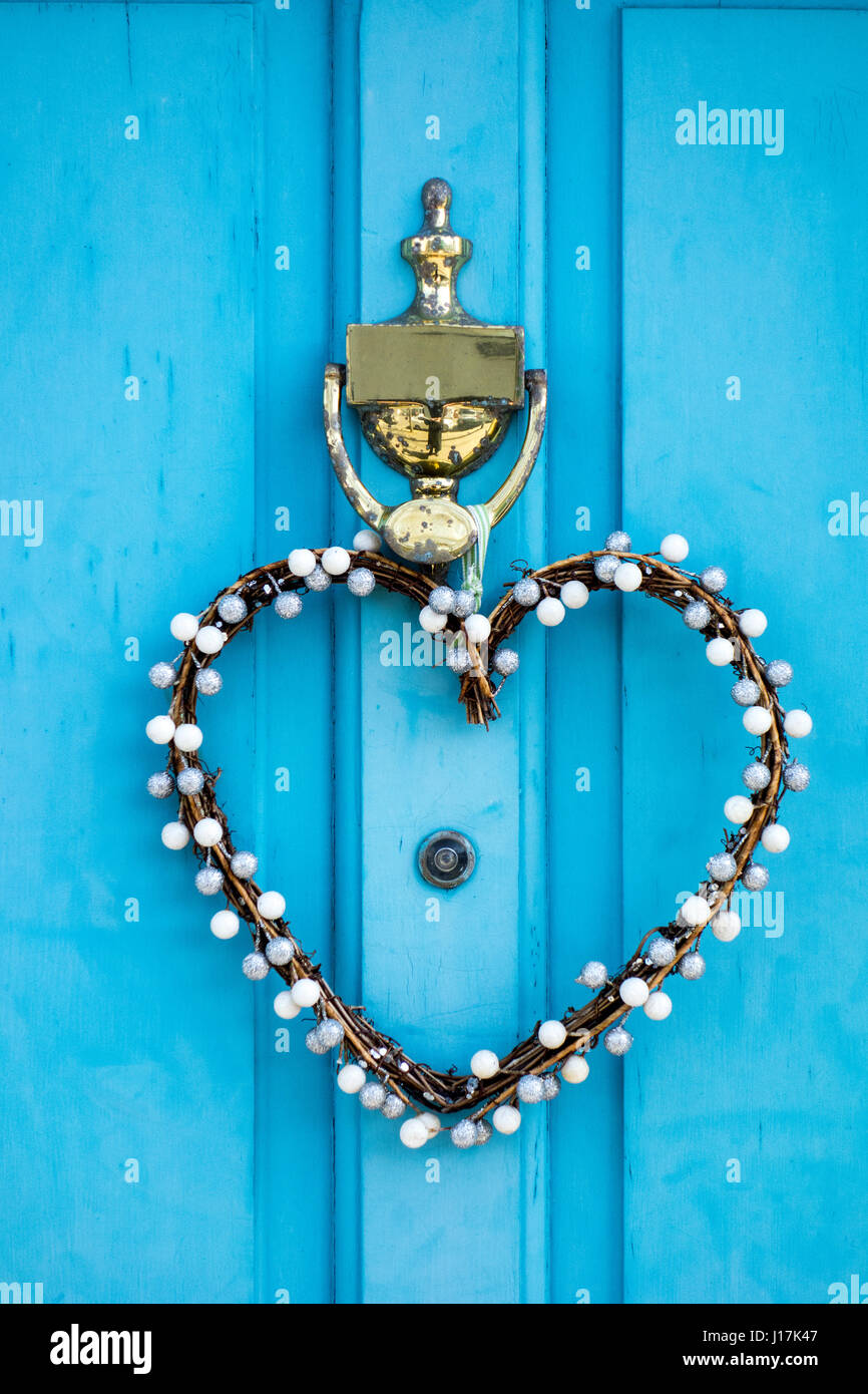 St. Valentines Day heart wreath hanging from a brass knocker on a turquoise coloured door - Stock Image
