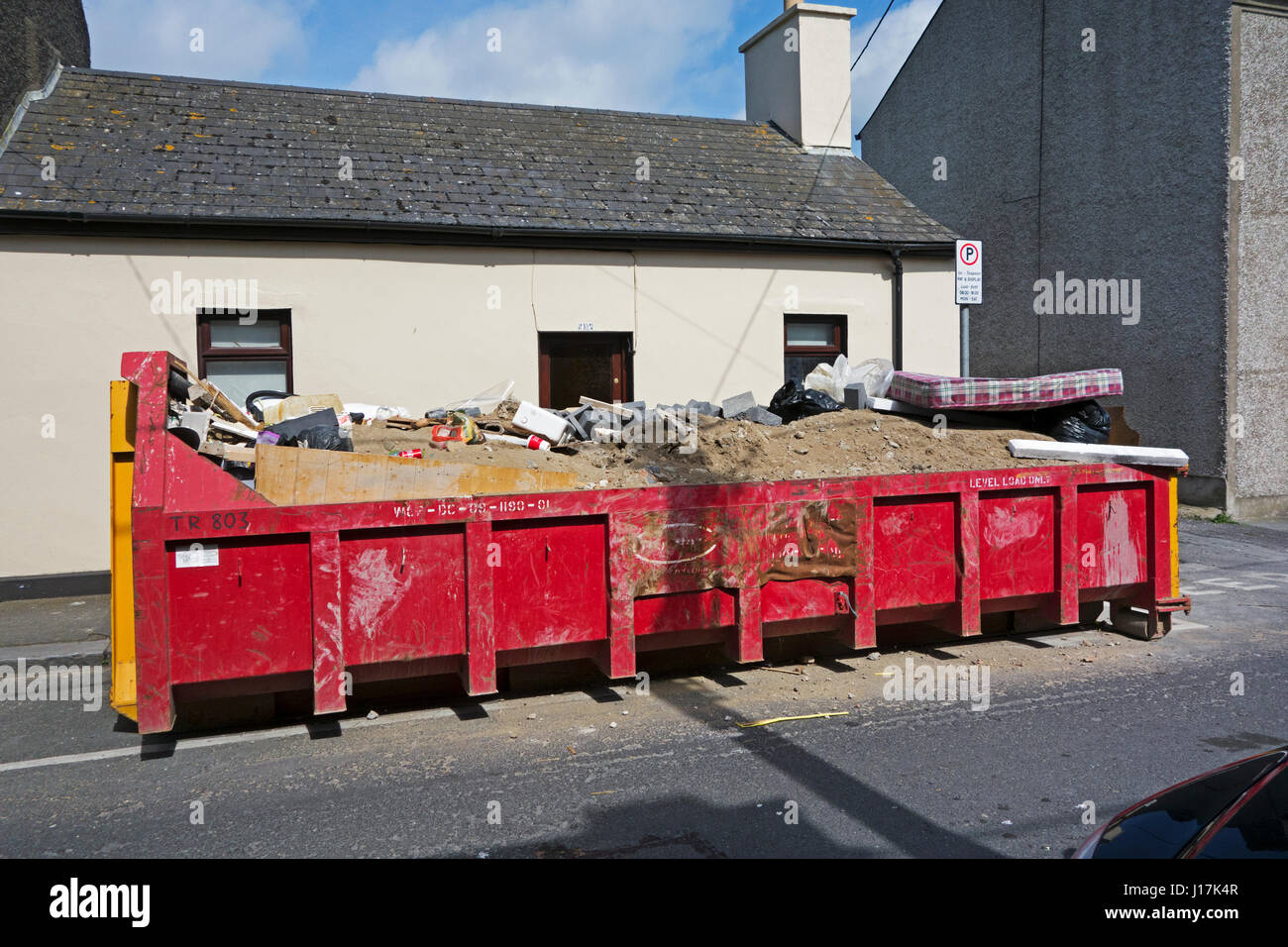 A fully laden large builders skip on an Irish street with earth and debris - Stock Image