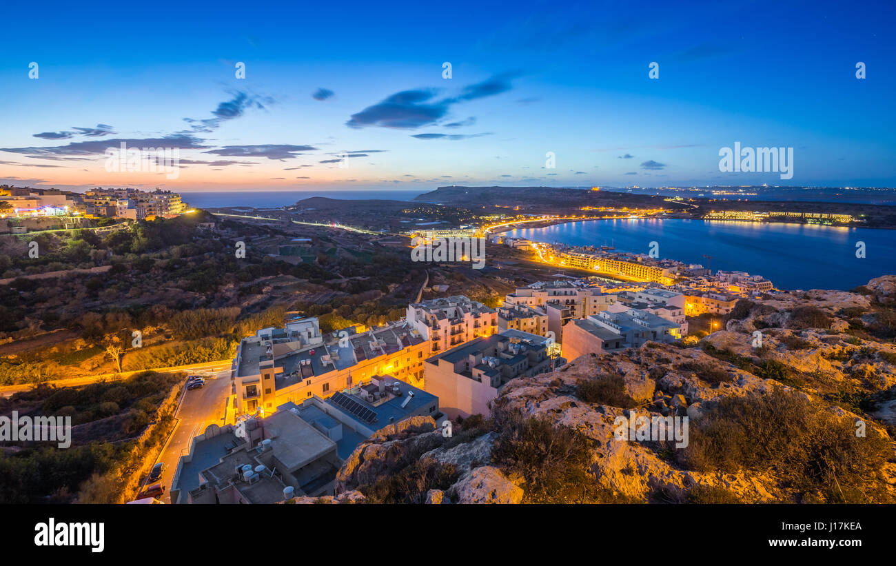 Il-Mellieha, Malta - Beautiful panoramic skyline view of Mellieha bay after sunset with blue sky and clouds - Stock Image
