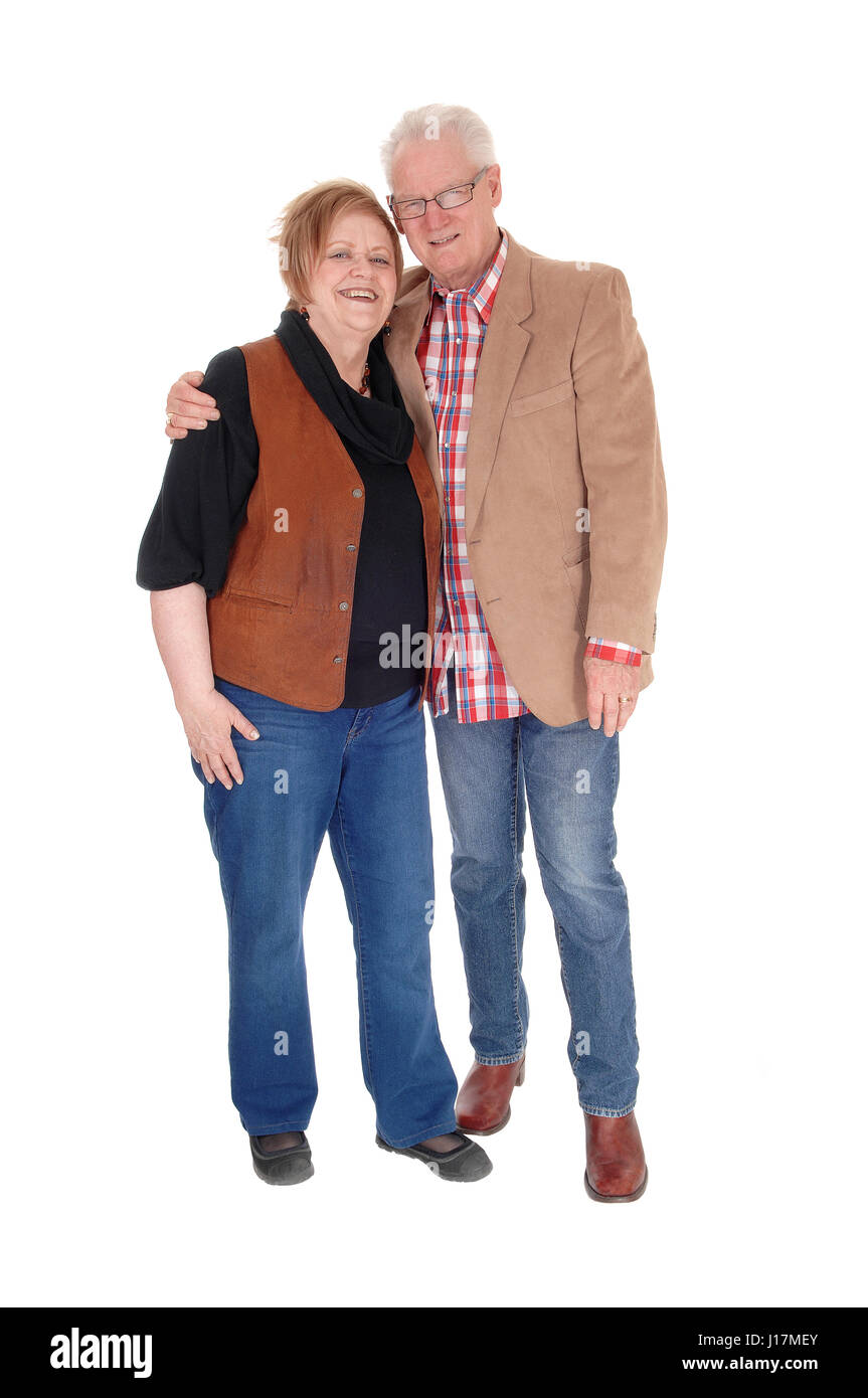A lovely older couple standing in casual clothing,  smiling, isolated for white background. - Stock Image