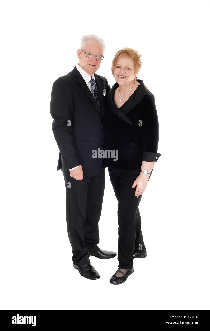A lovely older couple standing in suits, holding each other in full  lengths, isolated for white background. - Stock Image