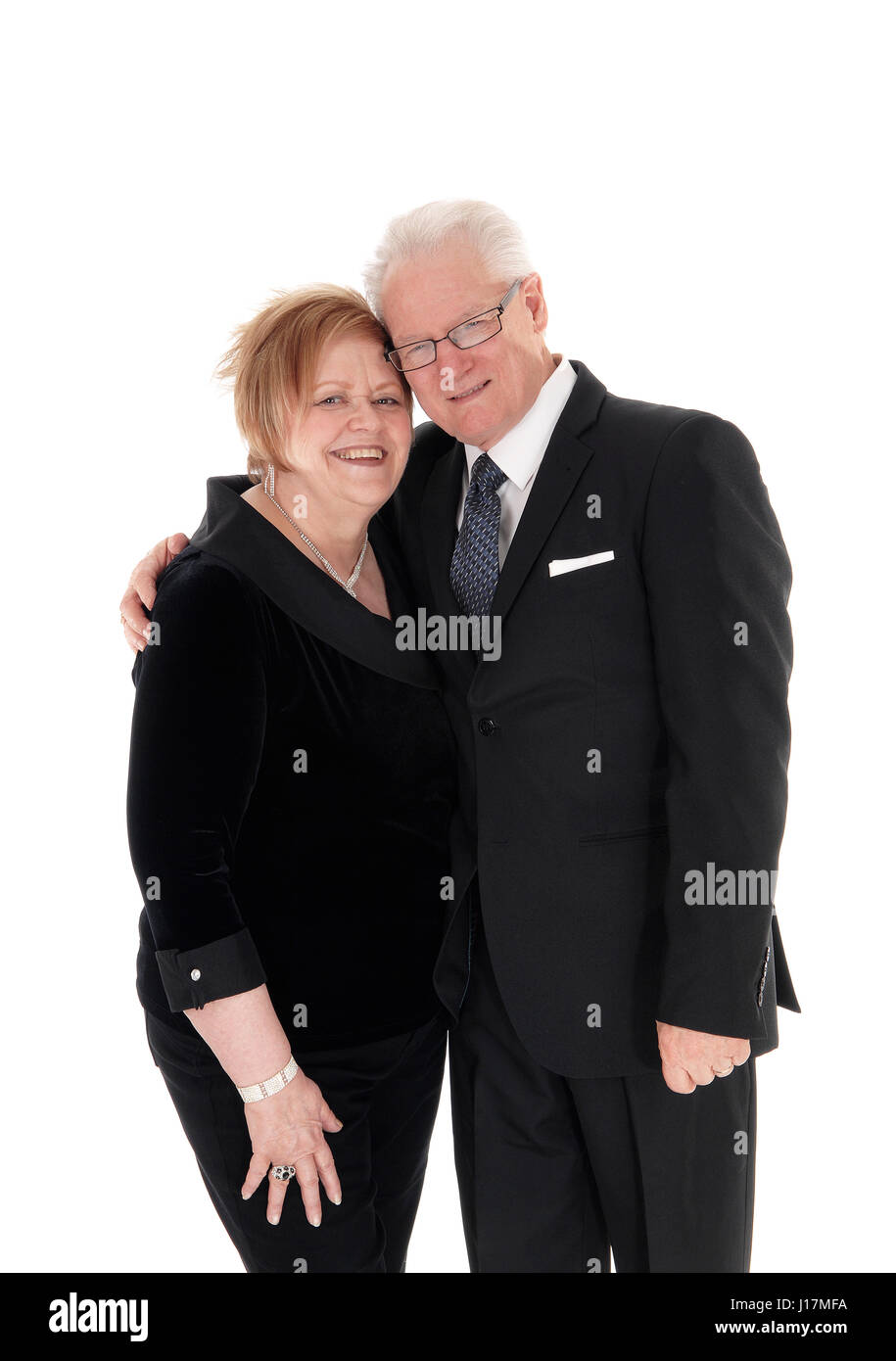 A lovely older couple standing in suits, hugging each other in full lengths isolated for white background. - Stock Image