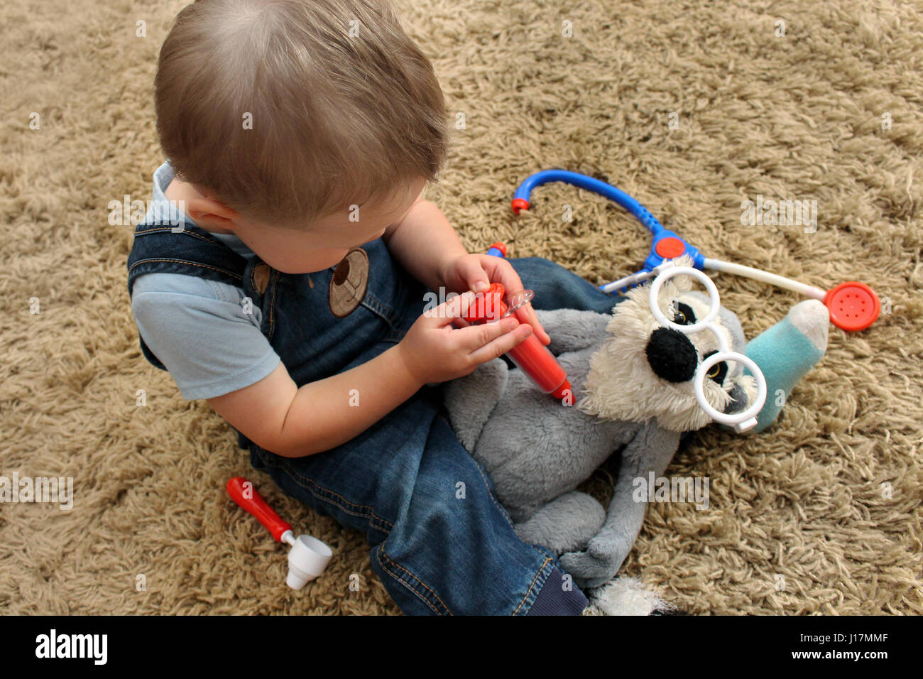 Toddler boy sitting on carpet playing doctor with his lemur stuffed toy - Stock Image
