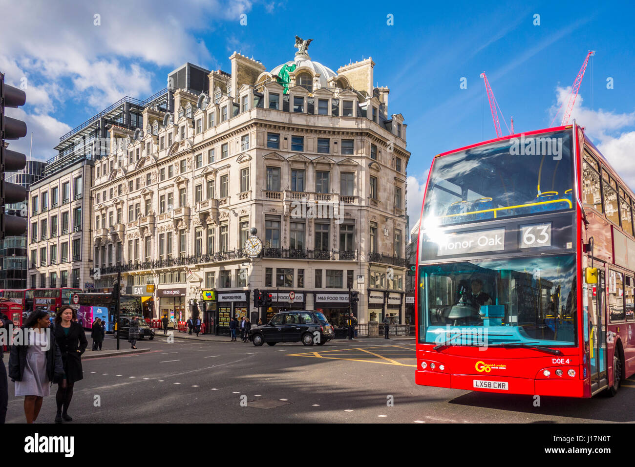 Red London bus driving accross Ludgate Circus in the City of London, UK - Stock Image
