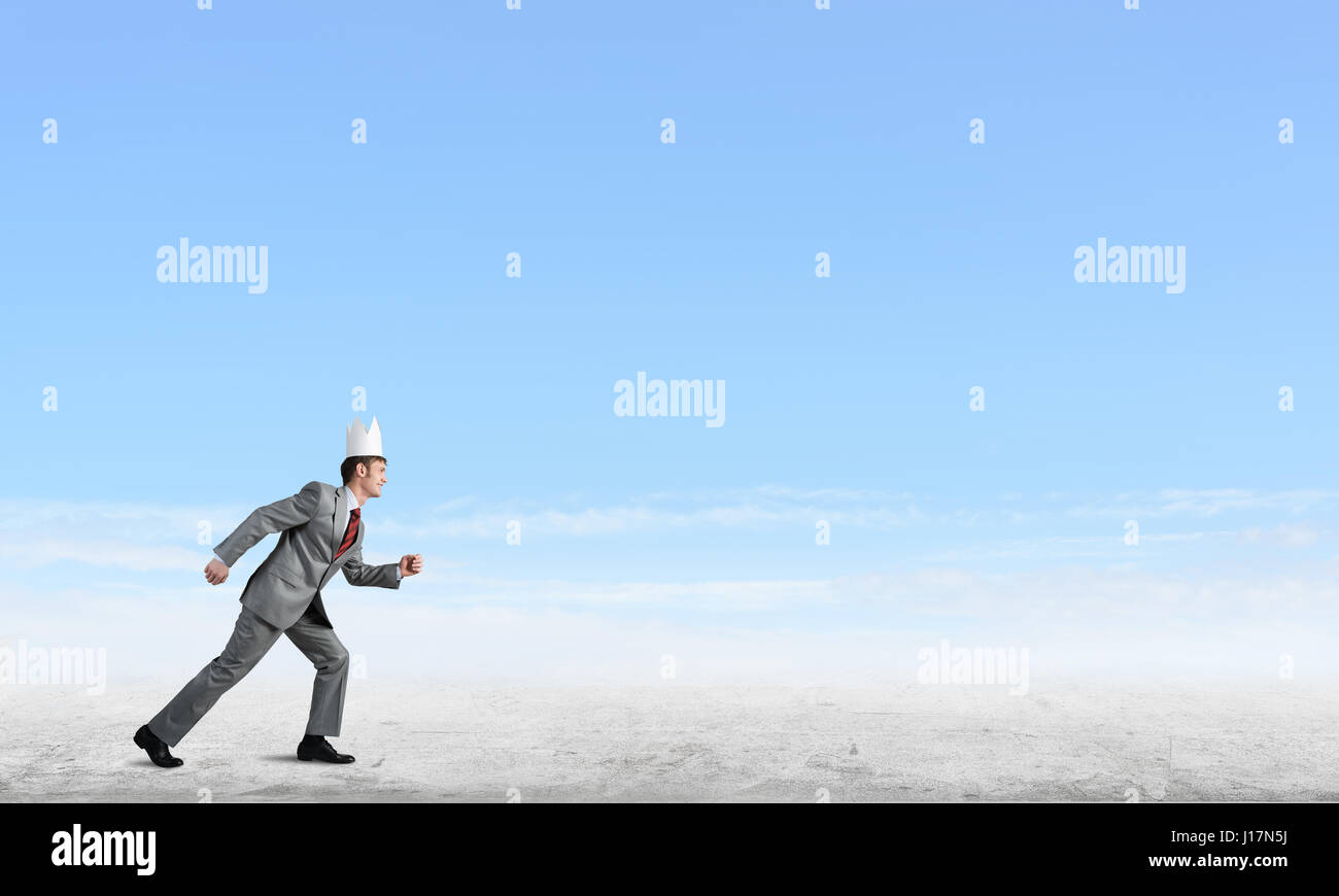 King businessman in elegant suit running and blue sky at background - Stock Image