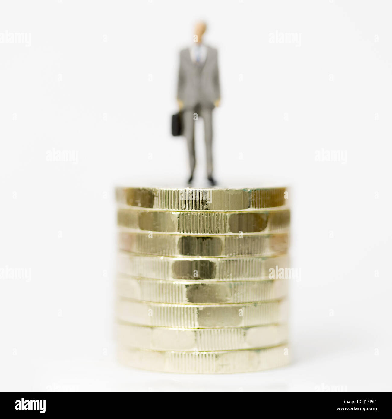 Close up/macro model stock photo depicting male wage worker on stack of new British pound coins. - Stock Image