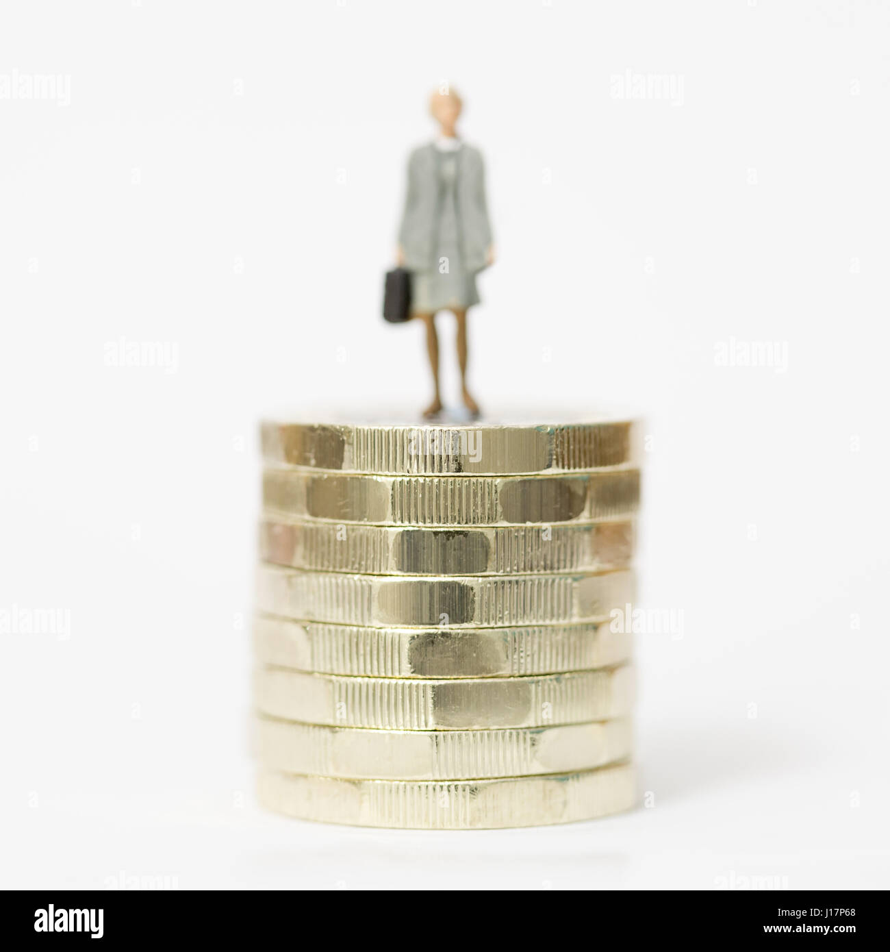 Close up/macro model stock photo depicting female wage worker on stack of new British pound coins. - Stock Image