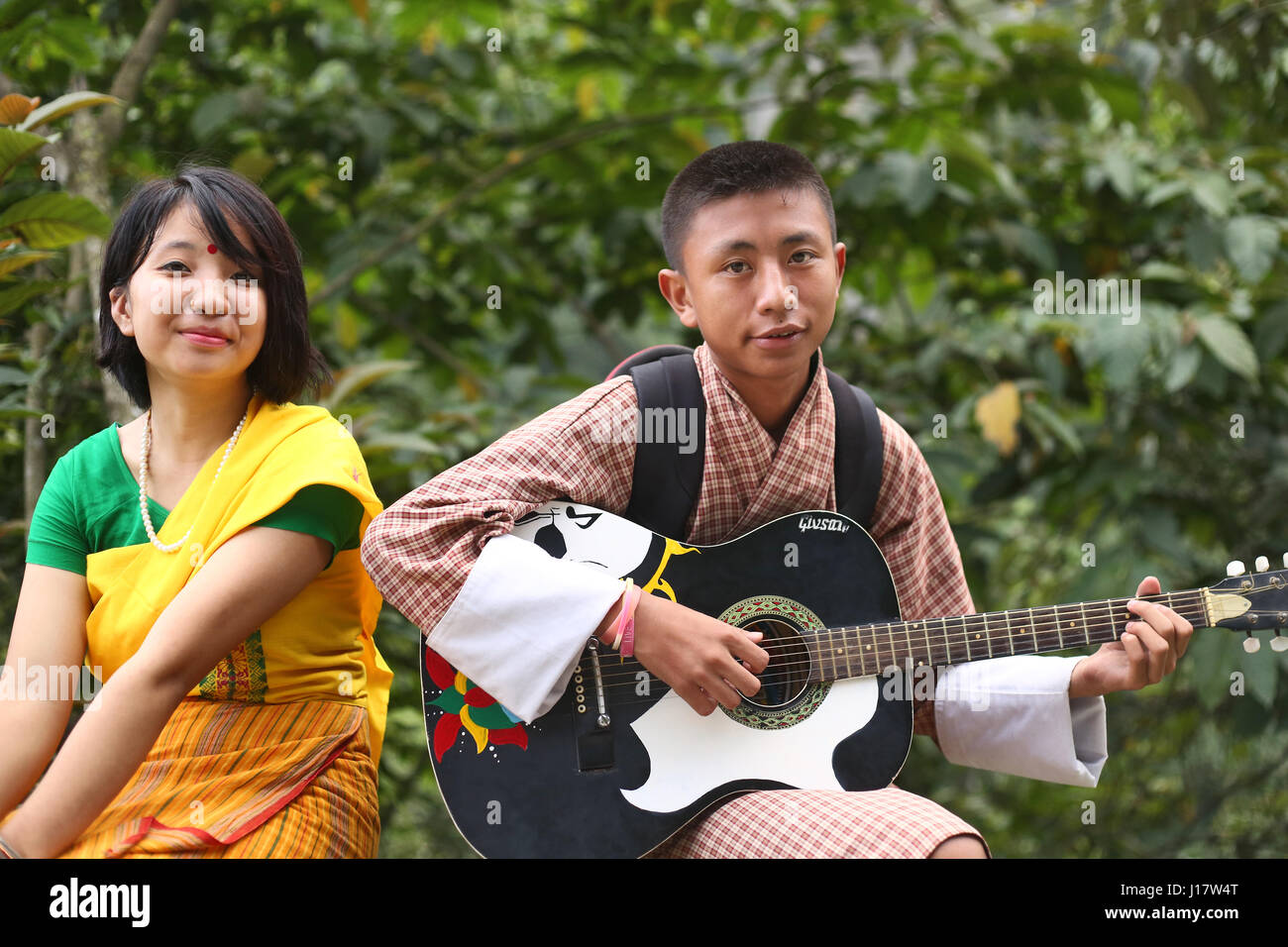 Bhutanese boy plying guitar and Bodo girl in traditional dress. Nganglam, Bhutan - Stock Image