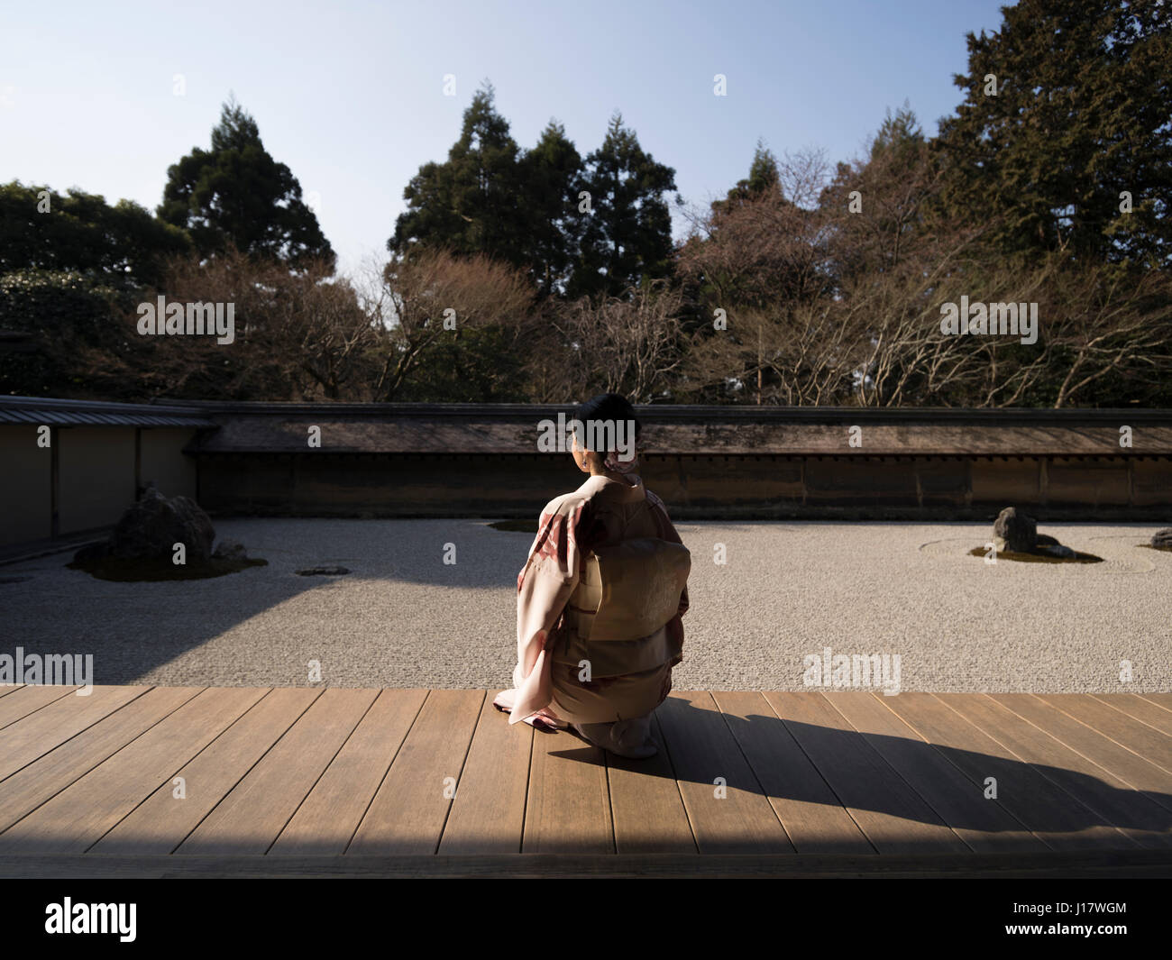 Young Japanese woman in kimono kneels beside The rock garden at Ryoan-ji, Kyoto. One of the finest examples of a - Stock Image