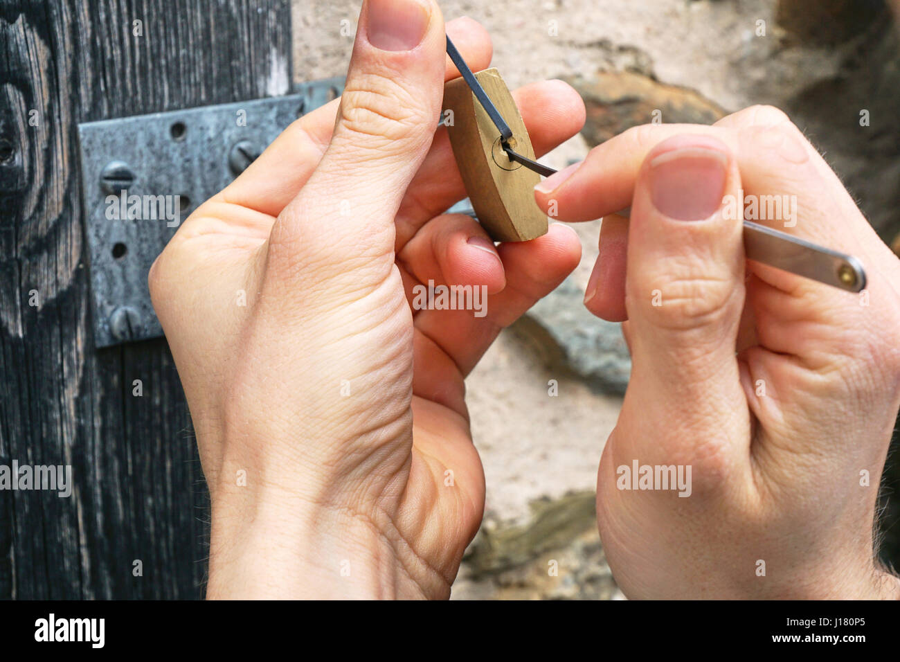 Key service, locksmith or burglar uses a lock-picking tool to open a wood door. Only hands, no persons. - Stock Image