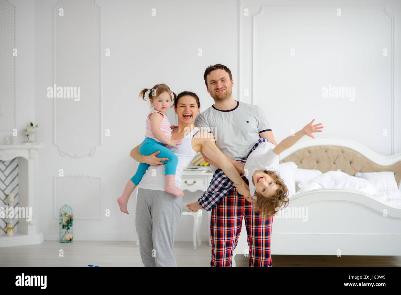 Cheerful beginning of day in a happy family. Cozy bedroom. Young parents hold on hands of the children. All are - Stock Image