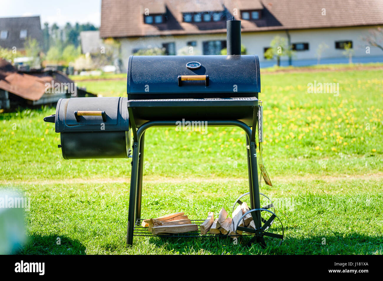 Preparing delicious meat in slow cooking smoker in backyard. Easy to use cylindrical smoker at family backyard barbecue - Stock Image