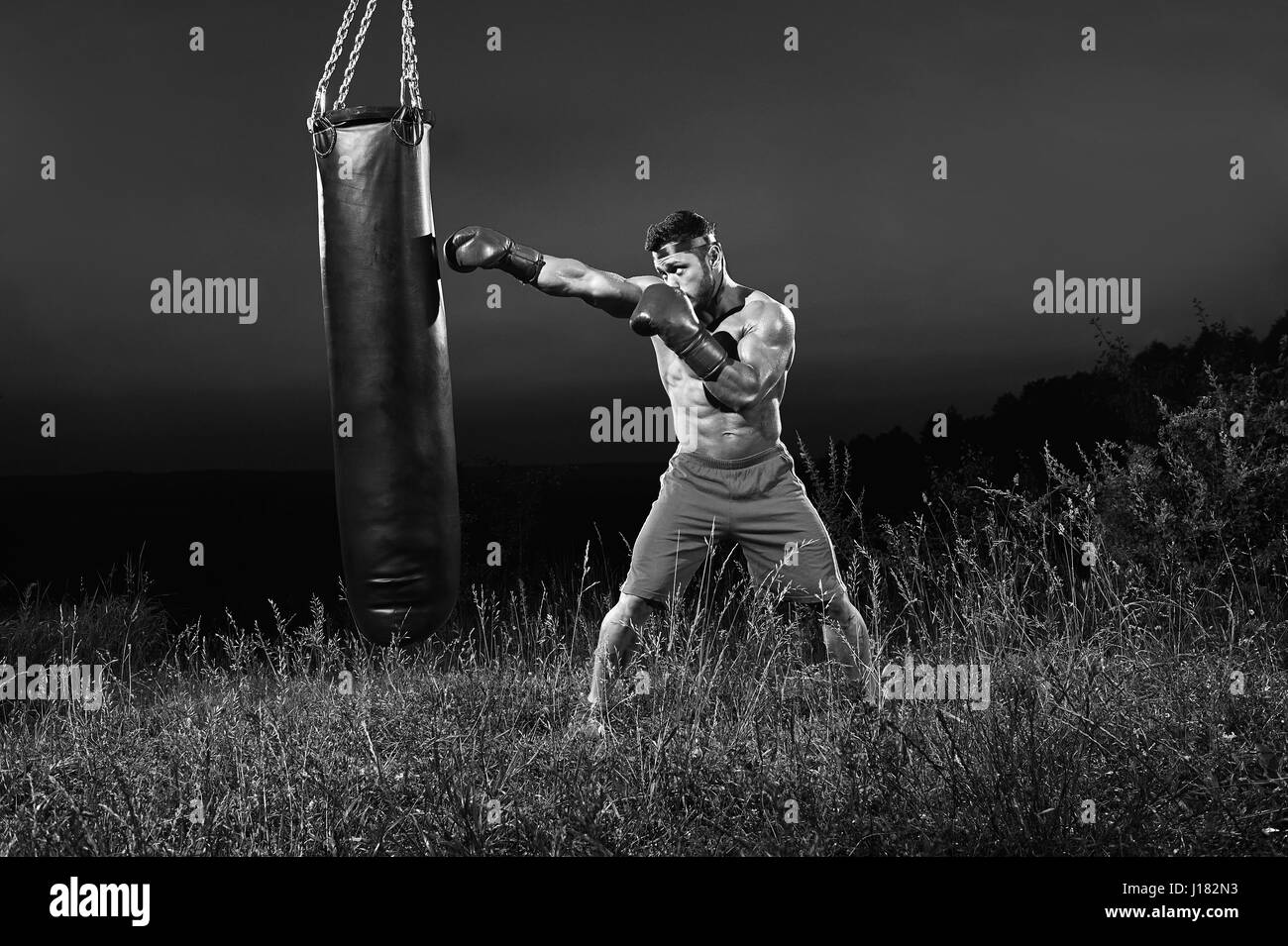 Monochrome shots of a male boxer training with a punching bag ou - Stock Image