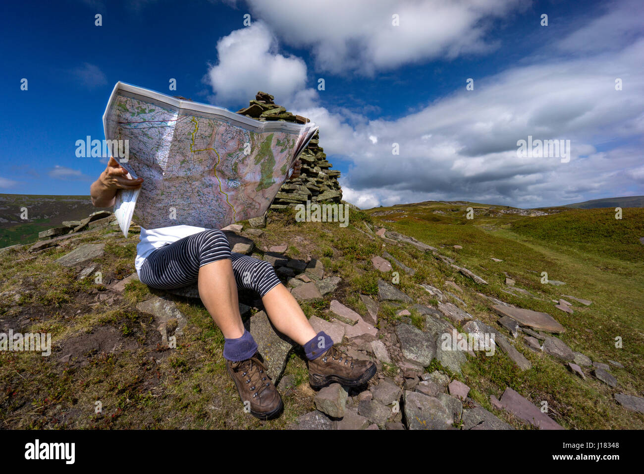 Woman hiker map reading in the Black Mountains, Brecon Beacons national park - Stock Image