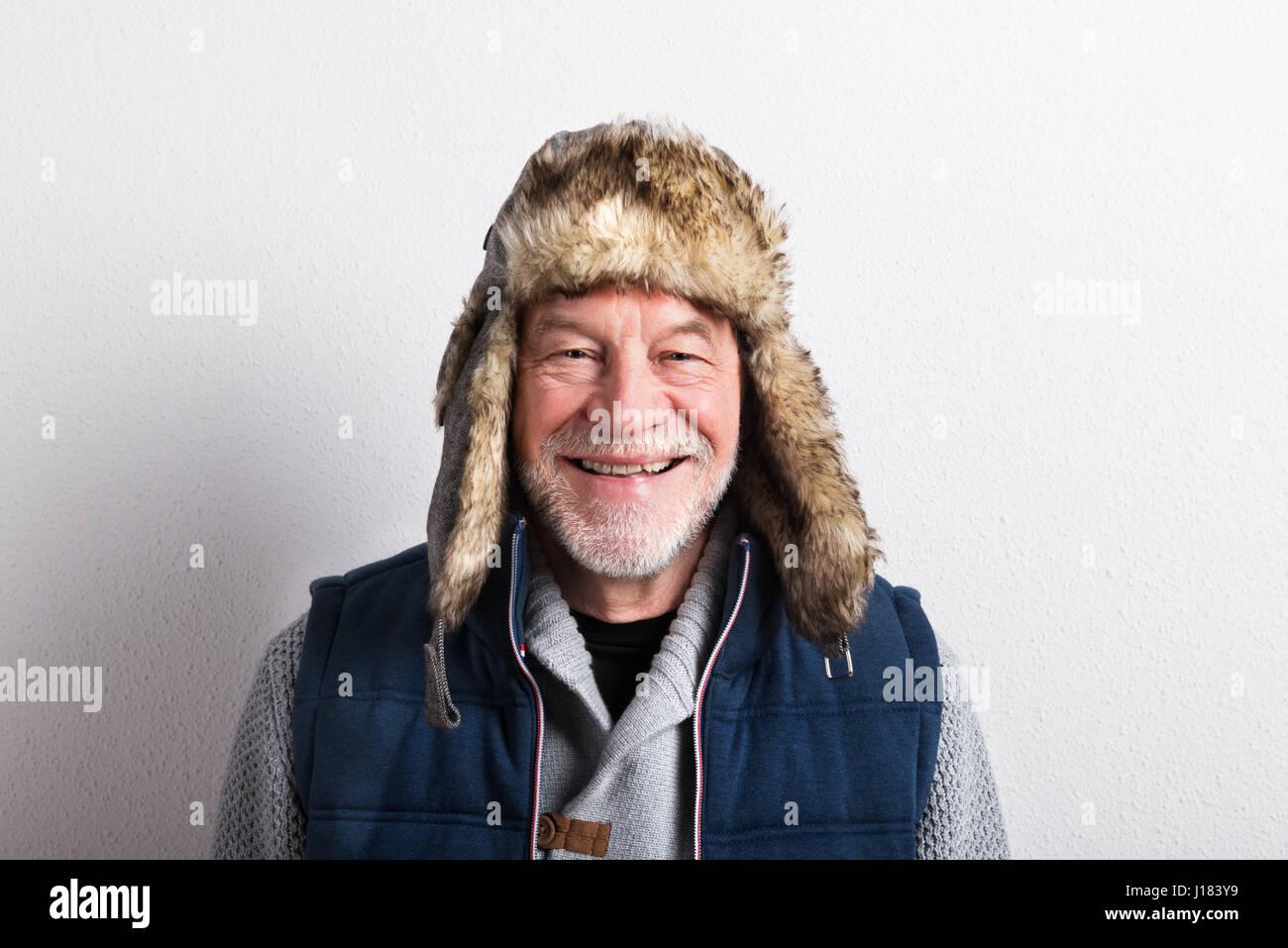 Senior man in sweater, vest jacket and fur hat, studio shot. - Stock Image