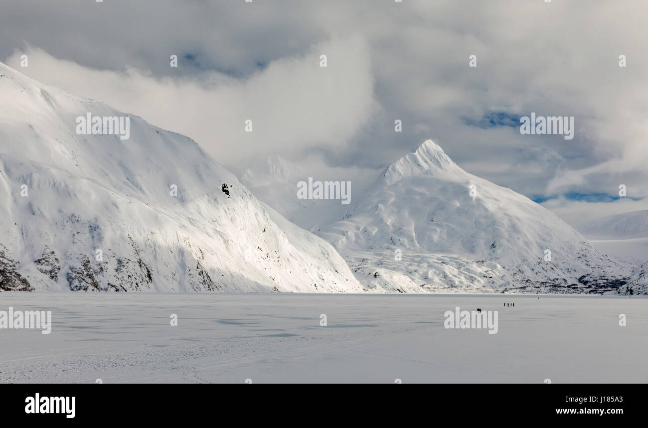 Hikers make the trek to Portage Glacier on Portage Lake in Southcentral Alaska. Winter. Afternoon. - Stock Image