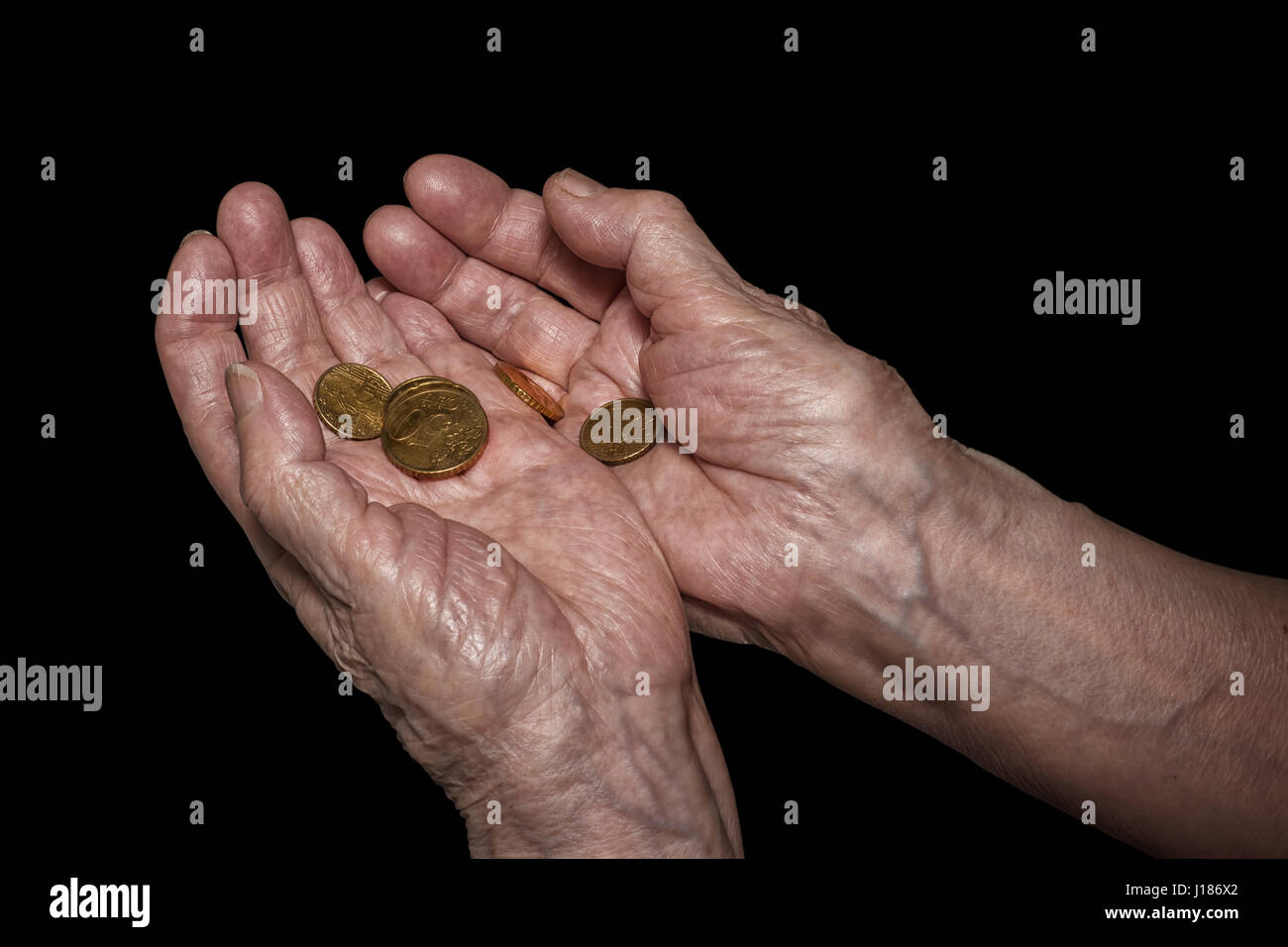 Senior woman hands holding some euro coins. Pension, poverty, social problems and senility theme. Isolated on black, - Stock Image