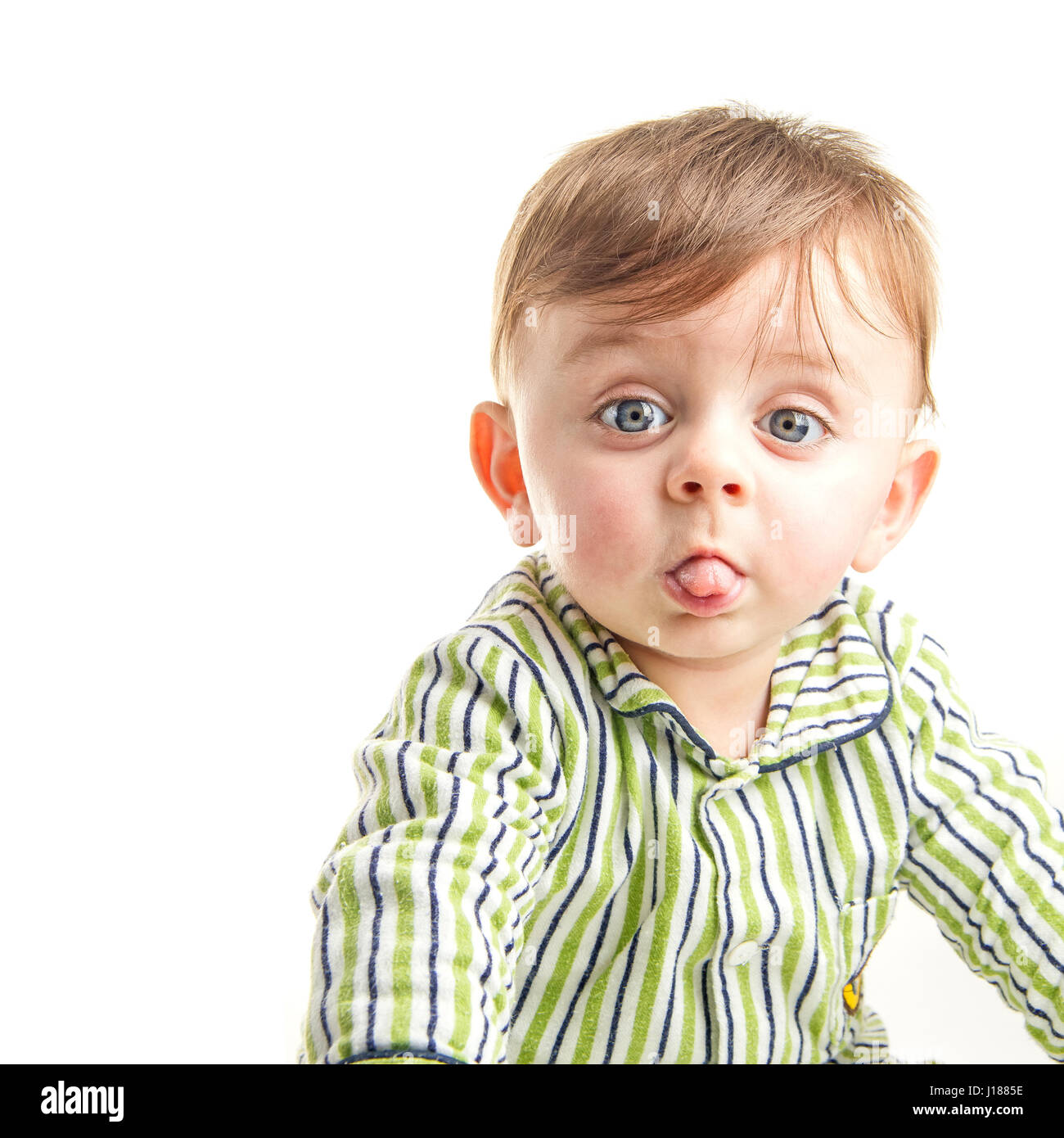 Baby grimacing to the camera on white background - Stock Image