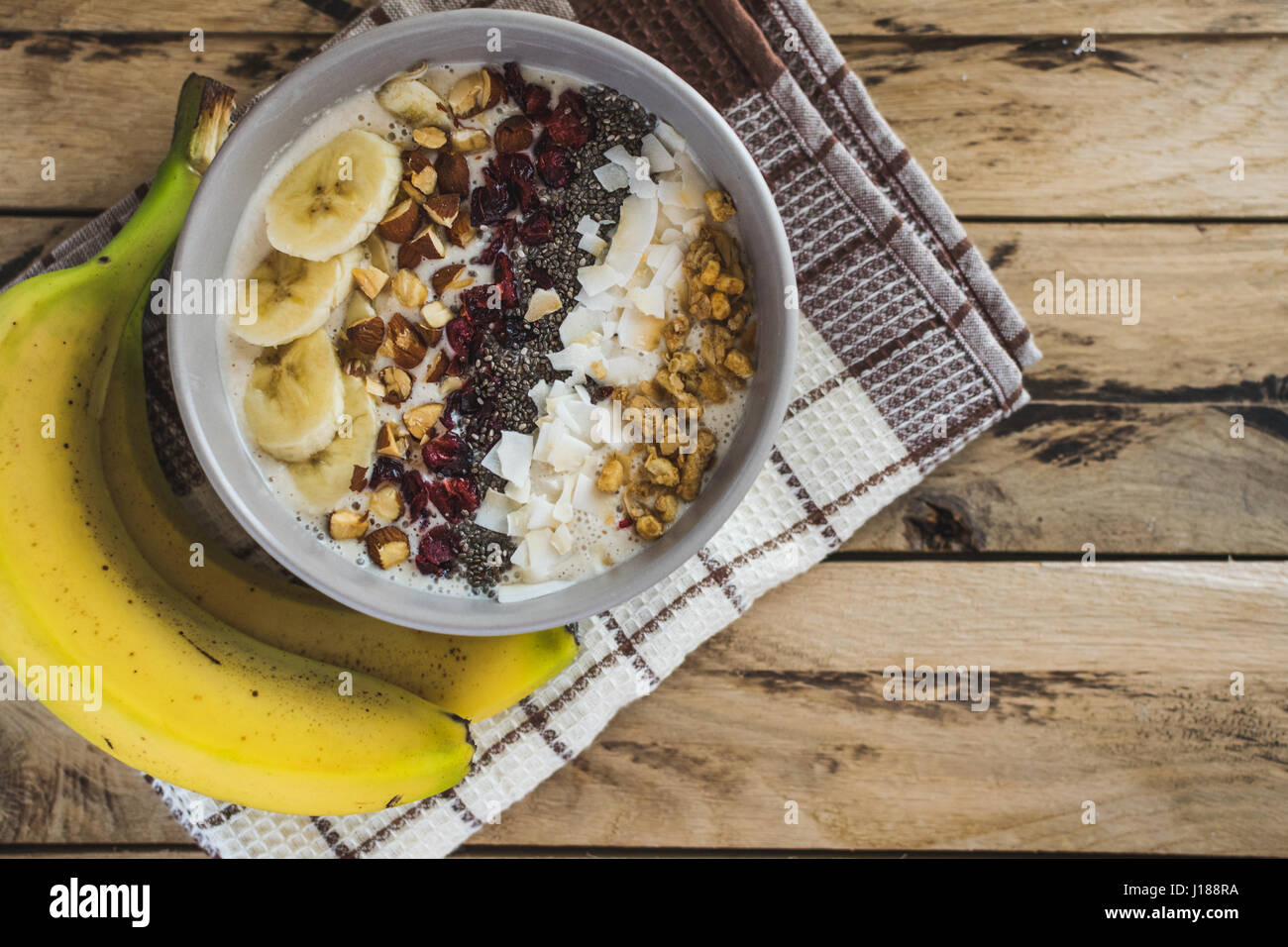 Oatmeal with bananas, cranberry, chia seeds, coconut shreds, almonds. Healthy breakfast concept. Rustic wooden background. - Stock Image