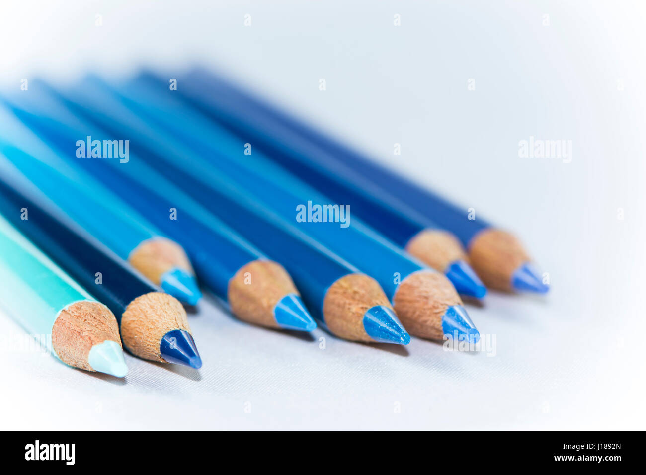 Eight blue pencils of different hues and shades lined up but stock