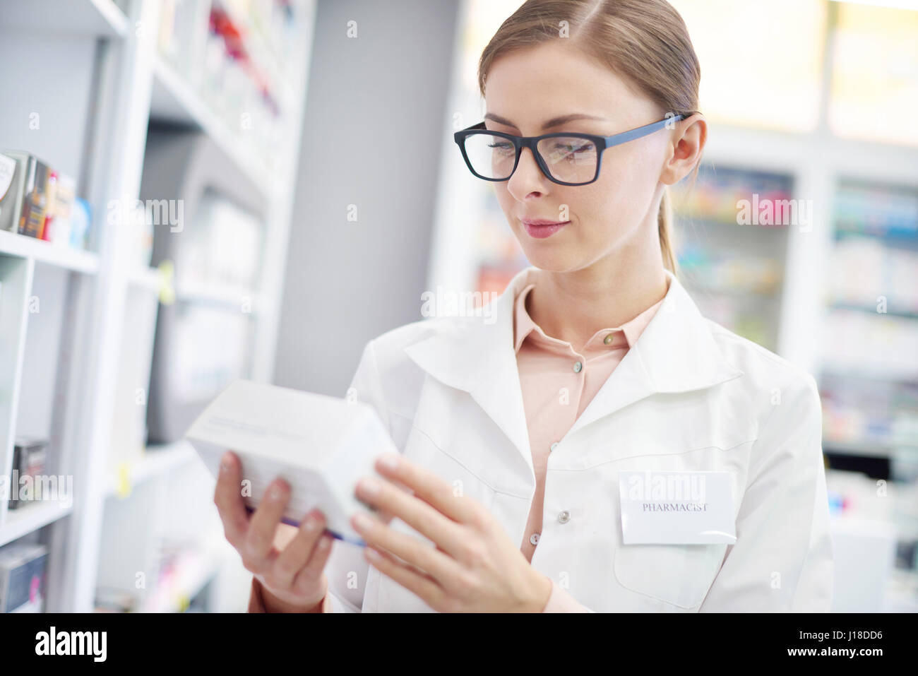 Female sales clerk studying composition of medicines - Stock Image