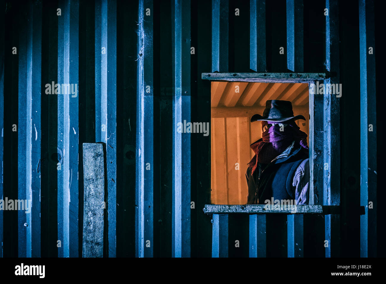 Masked man in the window of an outbuilding. - Stock Image