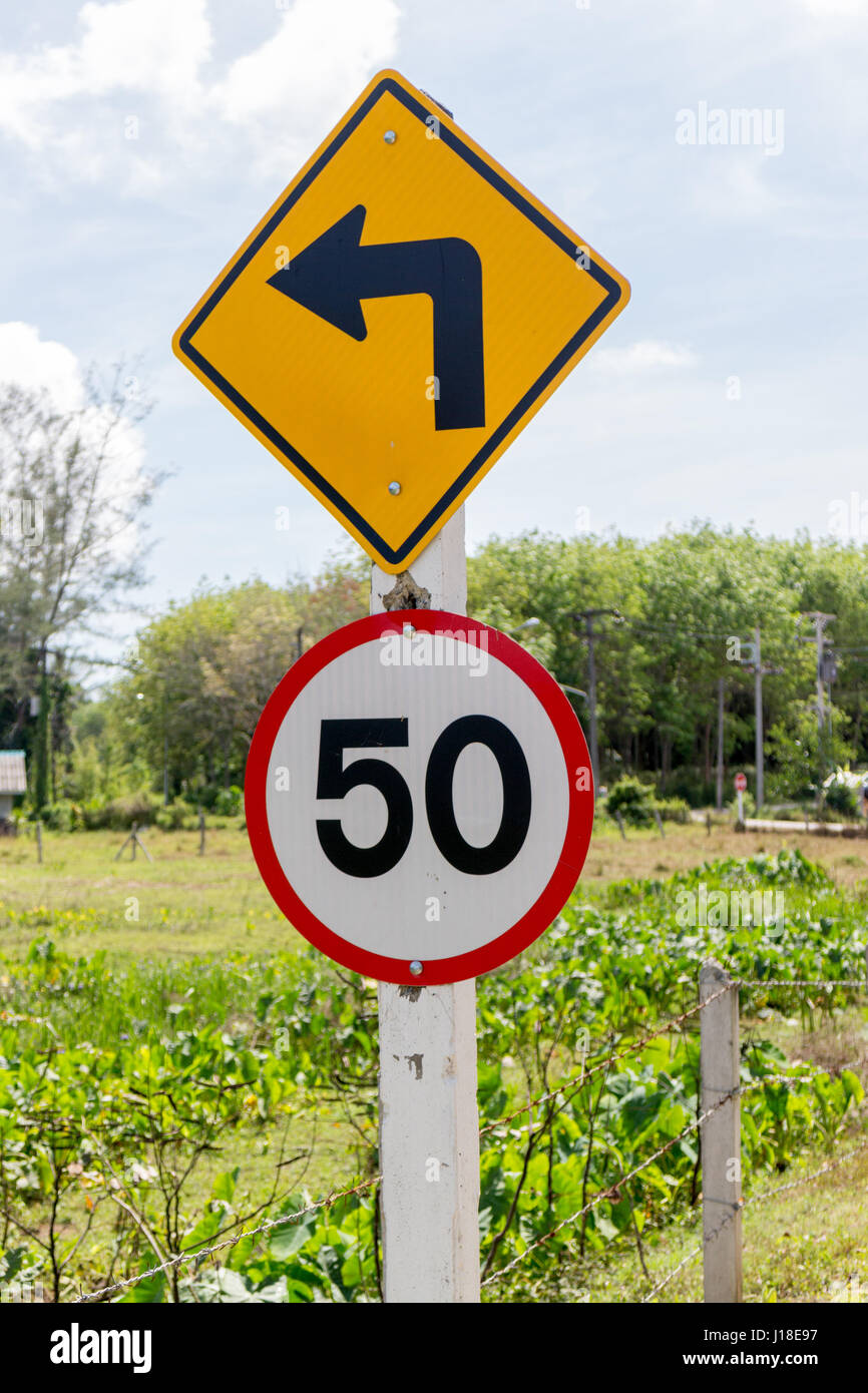 Direction arrow and 50 speed limit sign in rural setting - Stock Image