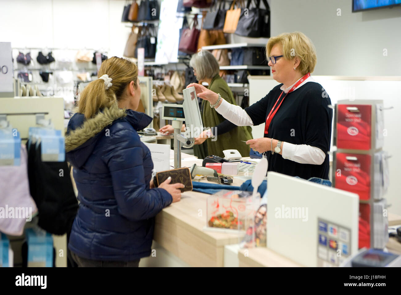ENSCHEDE, THE NETHERLANDS - APRIL 13, 2017: A woman is paying at a cashier after she bought clothes in clothes store - Stock Image