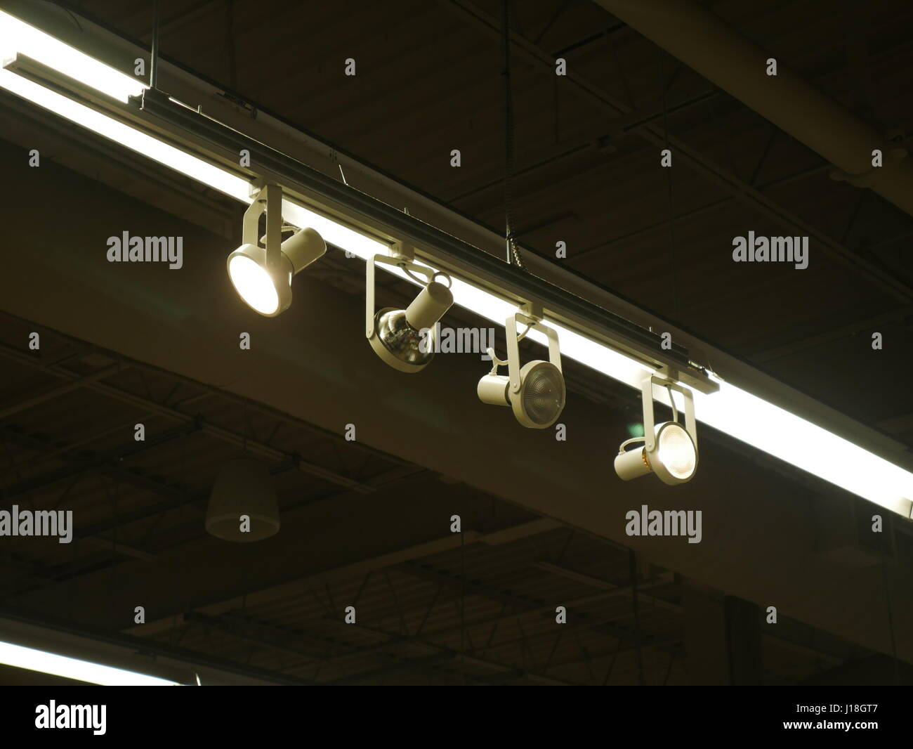 Set of spot lights on a rail hanging from the ceiling - Stock Image