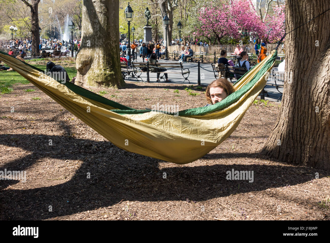 A young man relaxing in a hammock in Washington Square Park in New York - Stock Image