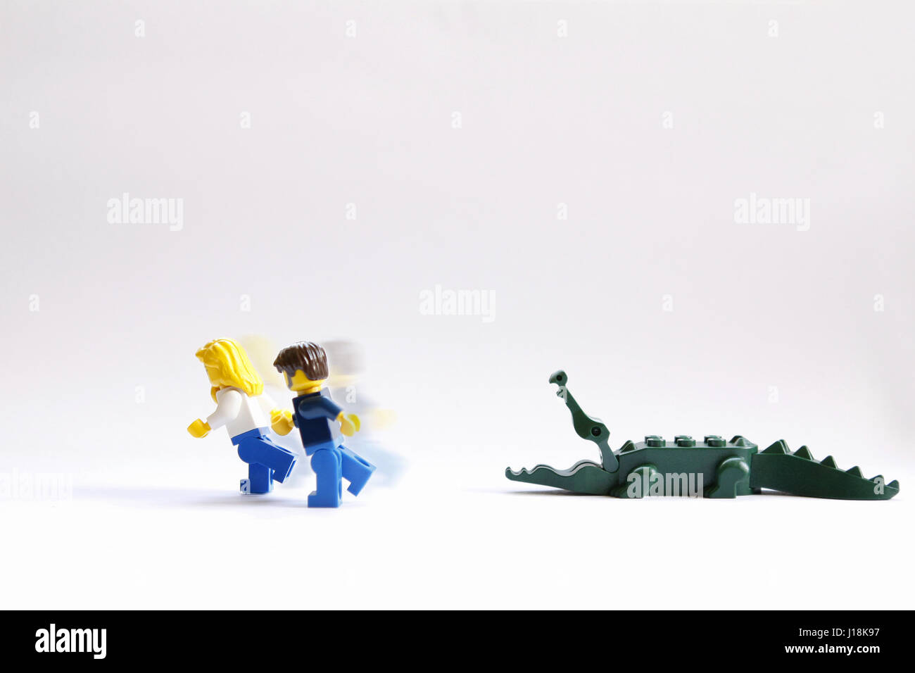 Male and female lego couple running scared from an alligator - Stock Image
