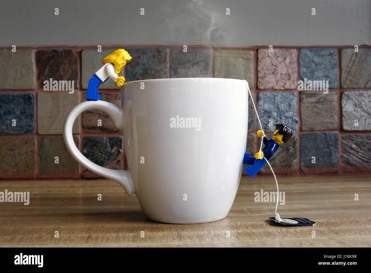 Male and female lego people climbing into a mug of tea - Stock Image