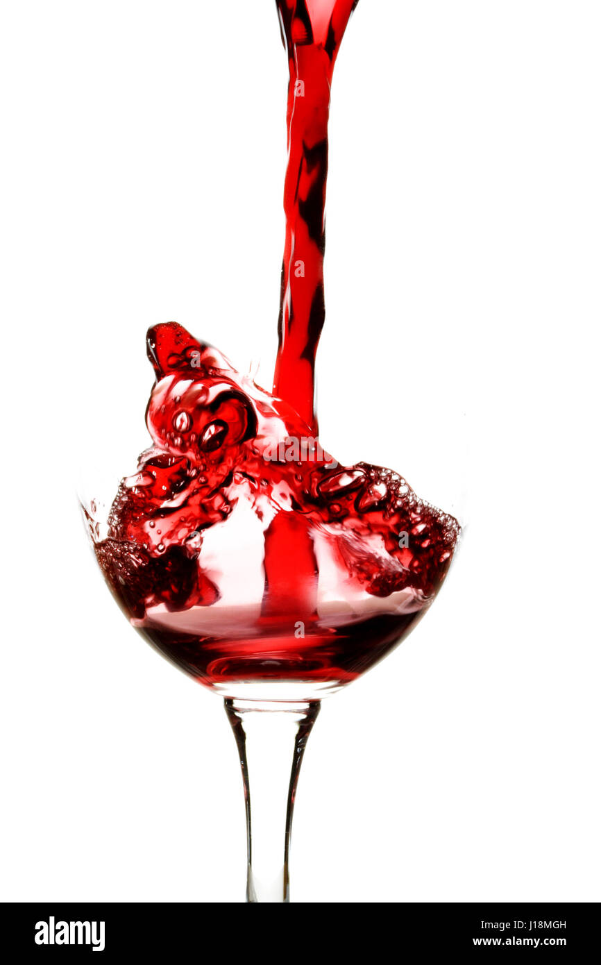 Pouring red wine into a wine glass - Stock Image