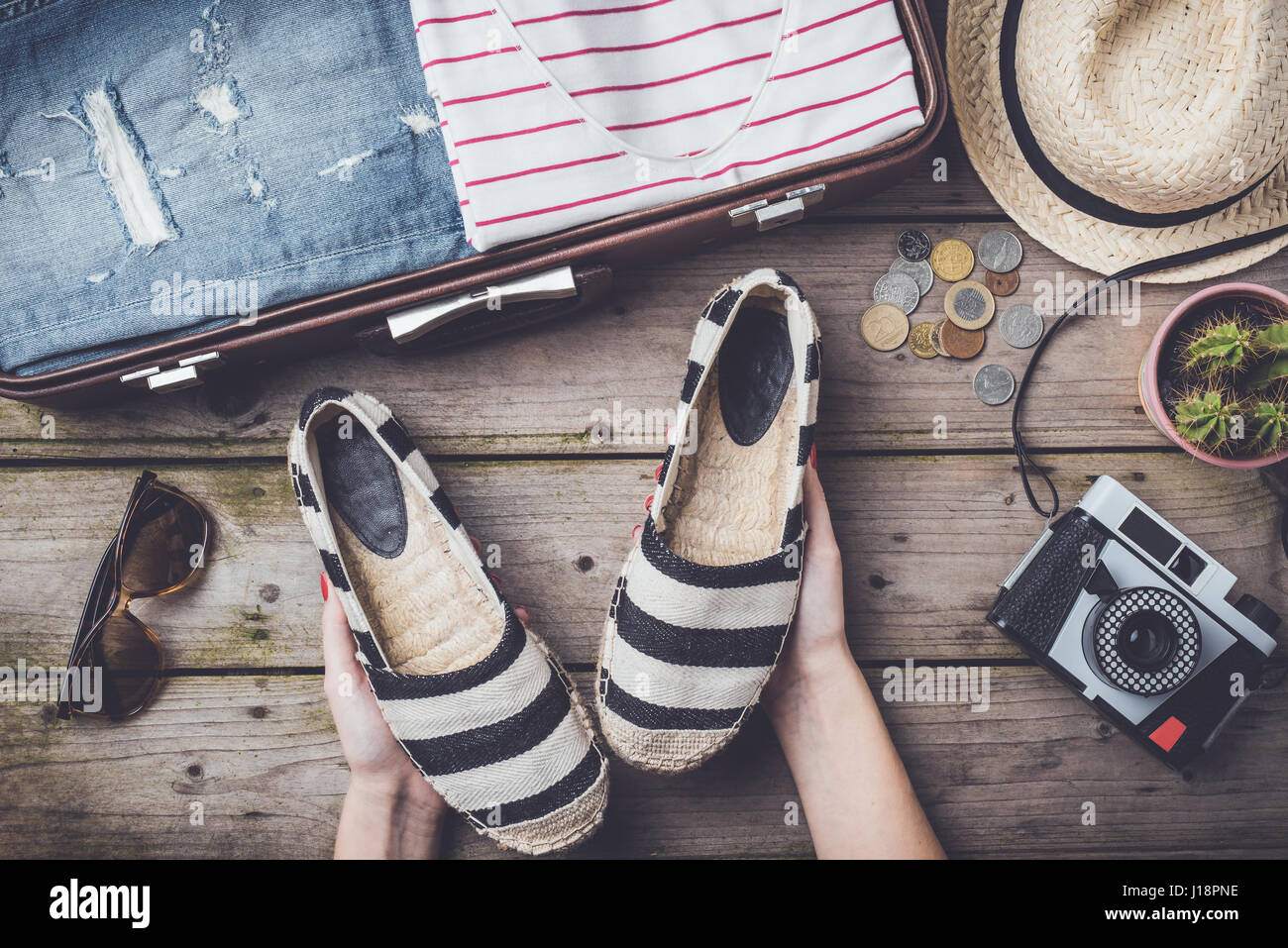 Travel preparations concept with suitcase, clothes and accessories on an old wooden table. Top view - Stock Image