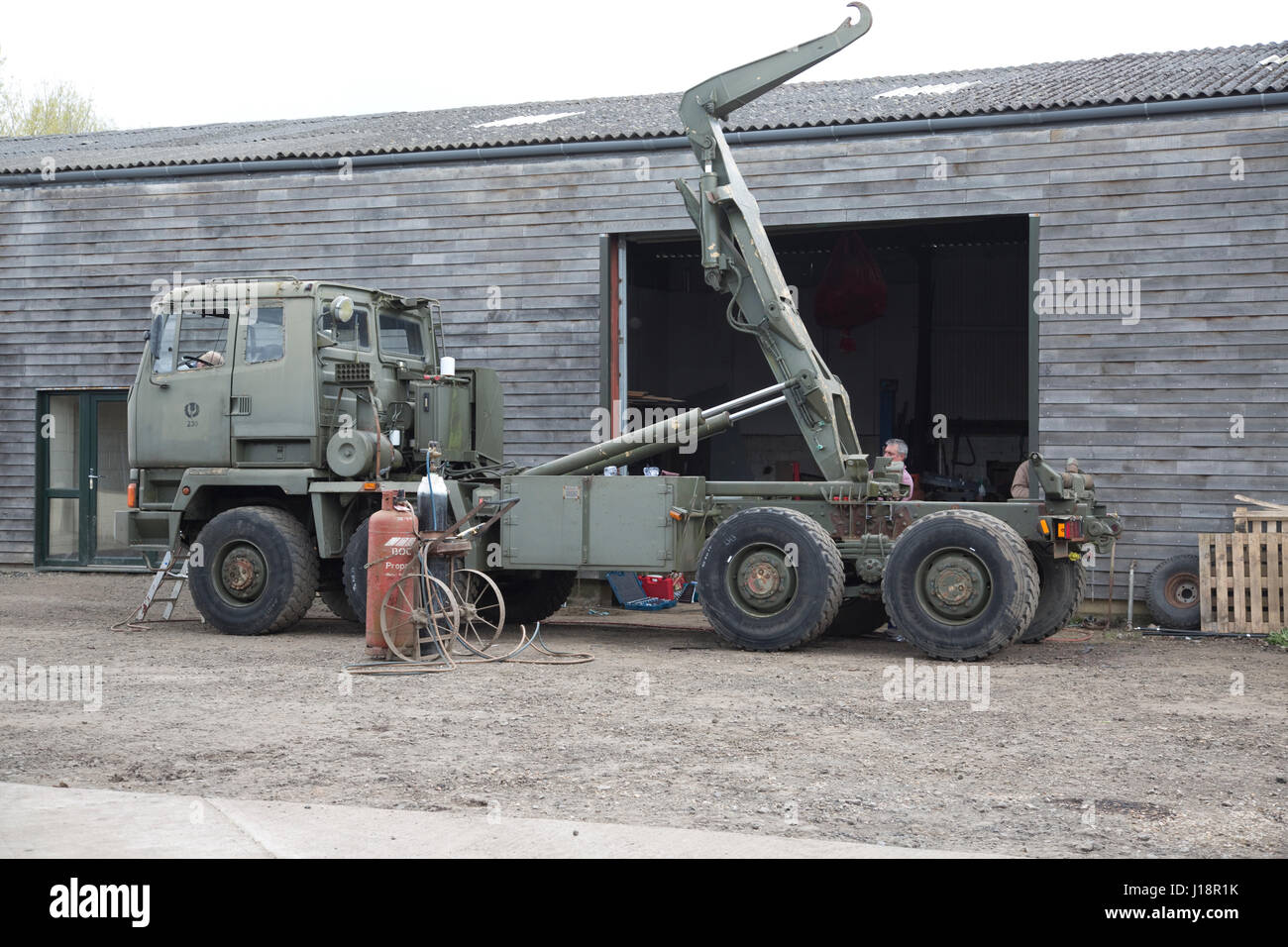 Ex army military 8WD all wheel drive khaki green truck with rear mounted crane lift being restored Cheltenham UK - Stock Image