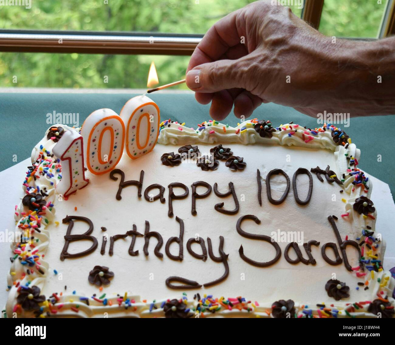 Hand Lighting A Candle On Decorated Cake For 100th Birthday