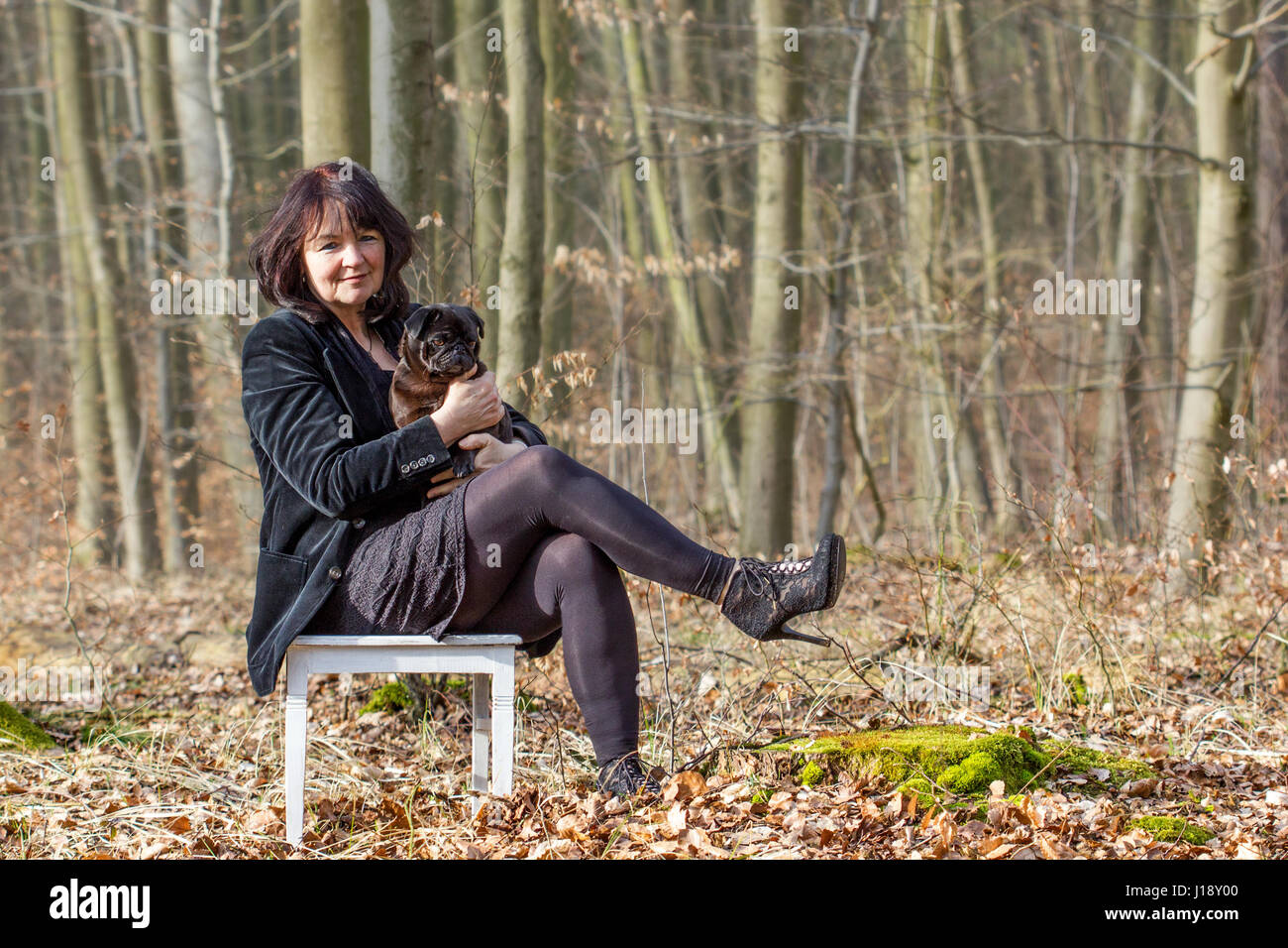 A woman in black clothes with a cute, black pug on a white chair - Stock Image